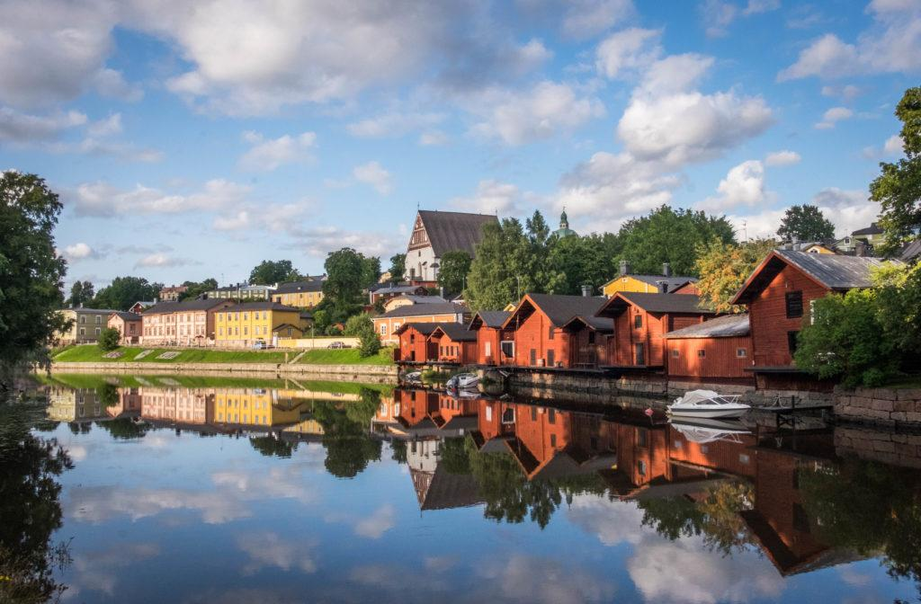 Red little cottages on a lake reflecting the blue and white cloudy sky in Porvoo, Finland.