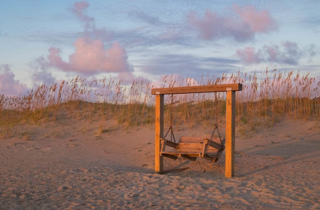 An empty swinging bench on the beach at sunrise on Tybee Island.