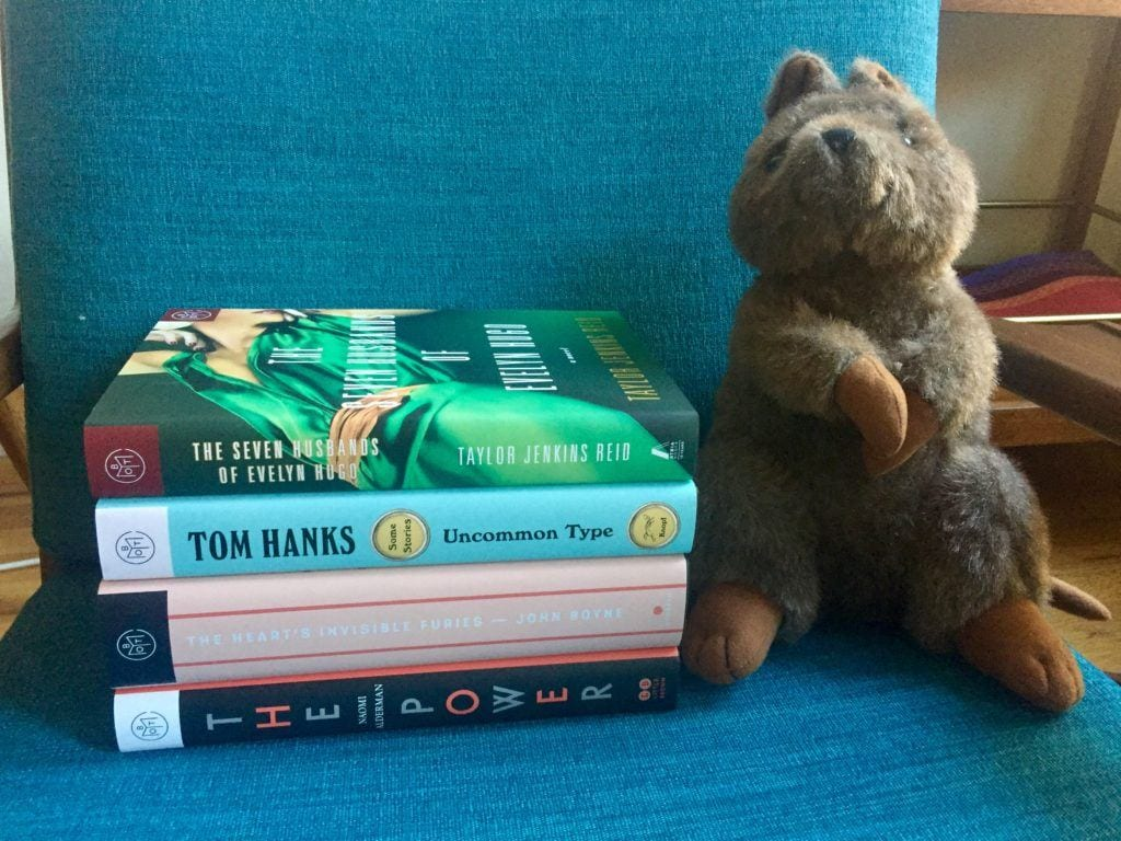 Kalbarri the stuffed Quokka next to a pile of books.