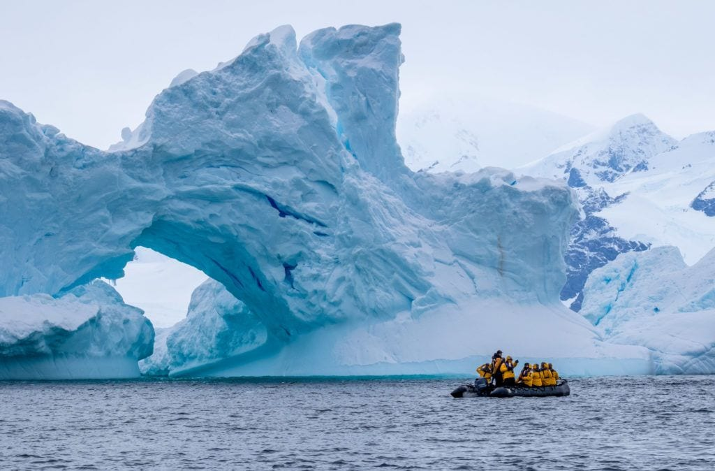 A tiny zodiac boat filled with around 15 passengers in front of a giant ice shape, bluish-white, in Antarctica.