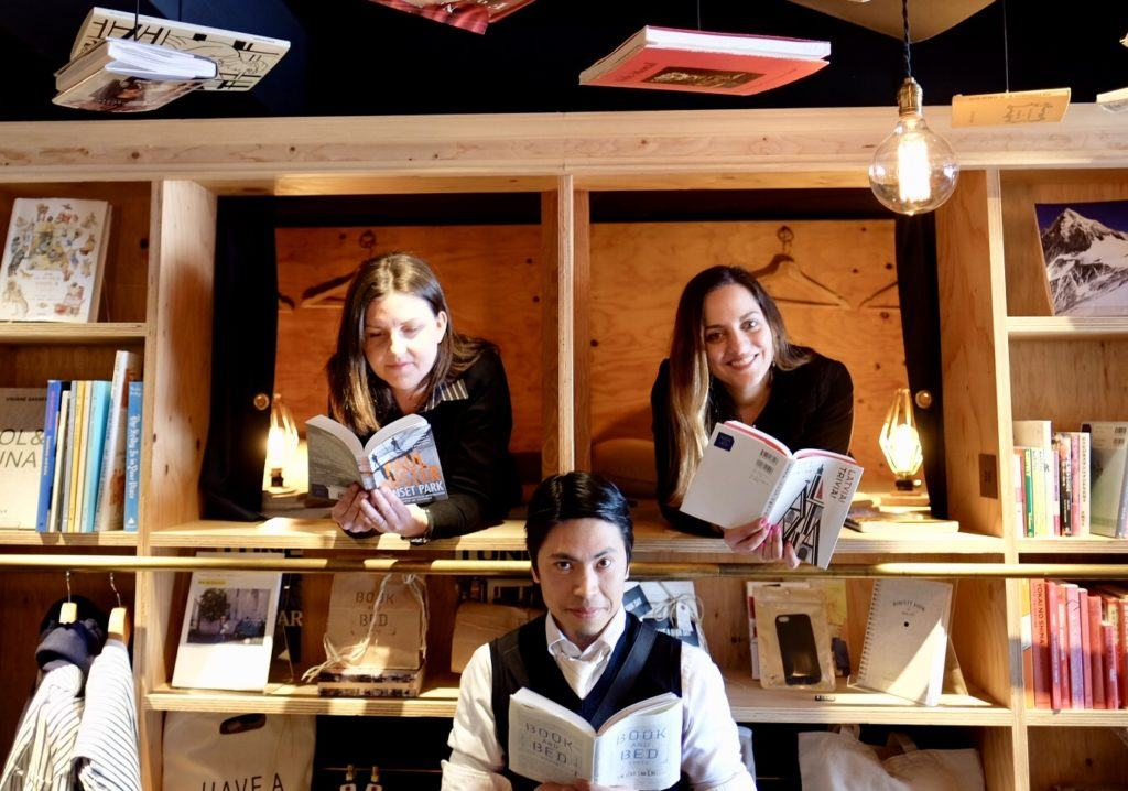 Kate and her friends Jess and Hai reading books at a hoot hostel in Tokyo.