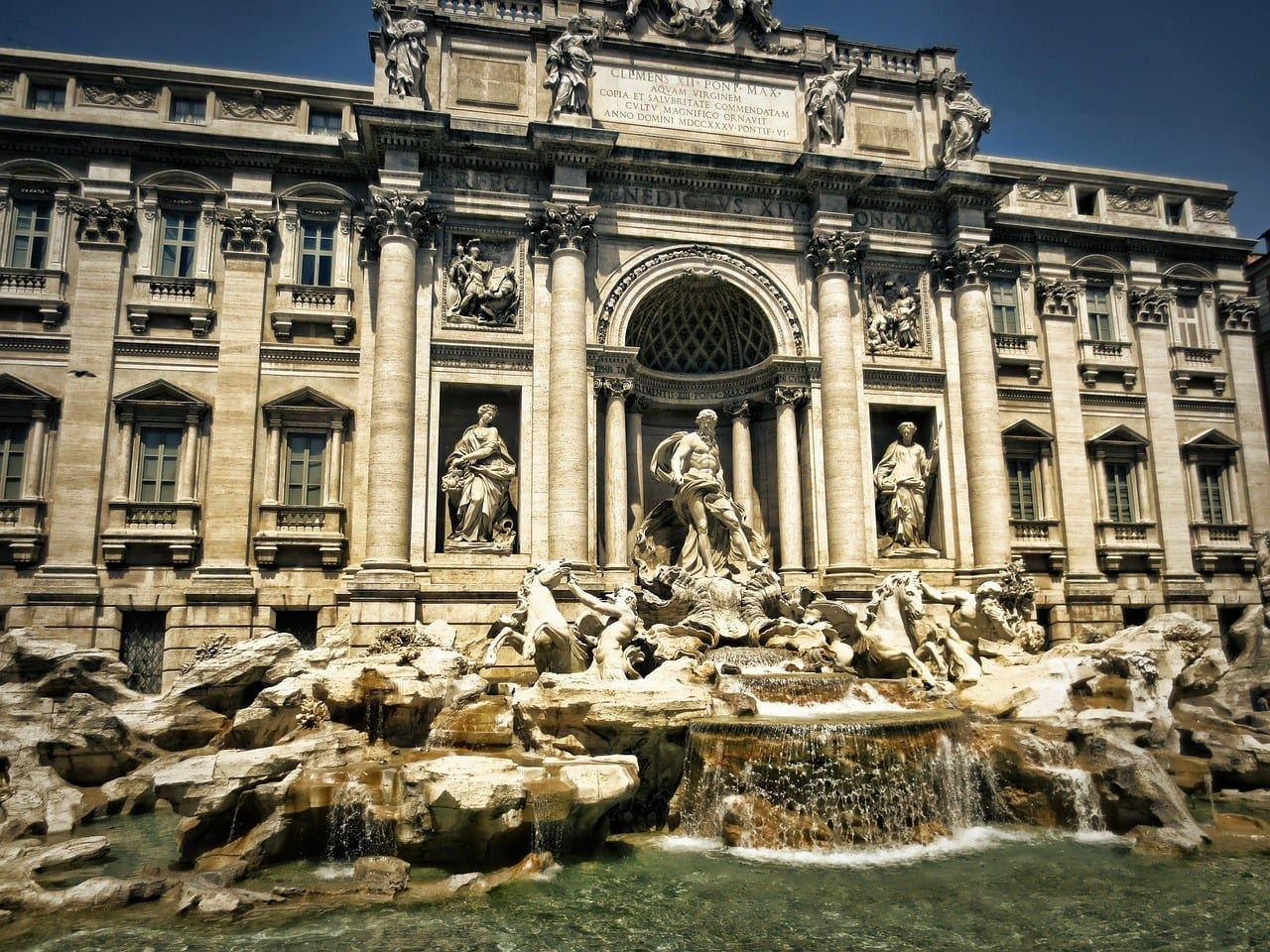 The Trevi Fountain, covered with Baroque era white marble statues and flowing water.