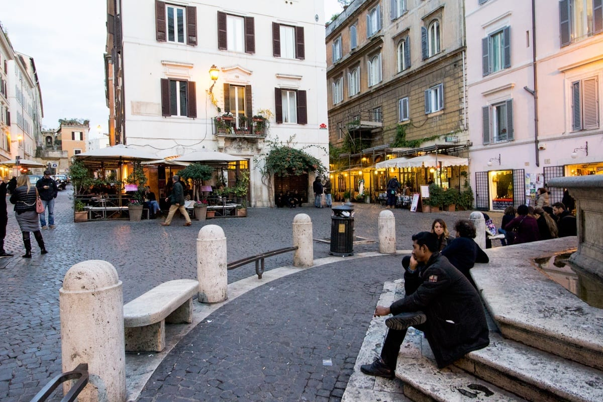 A man sitting at the base of a fountain in Monti, Rome.