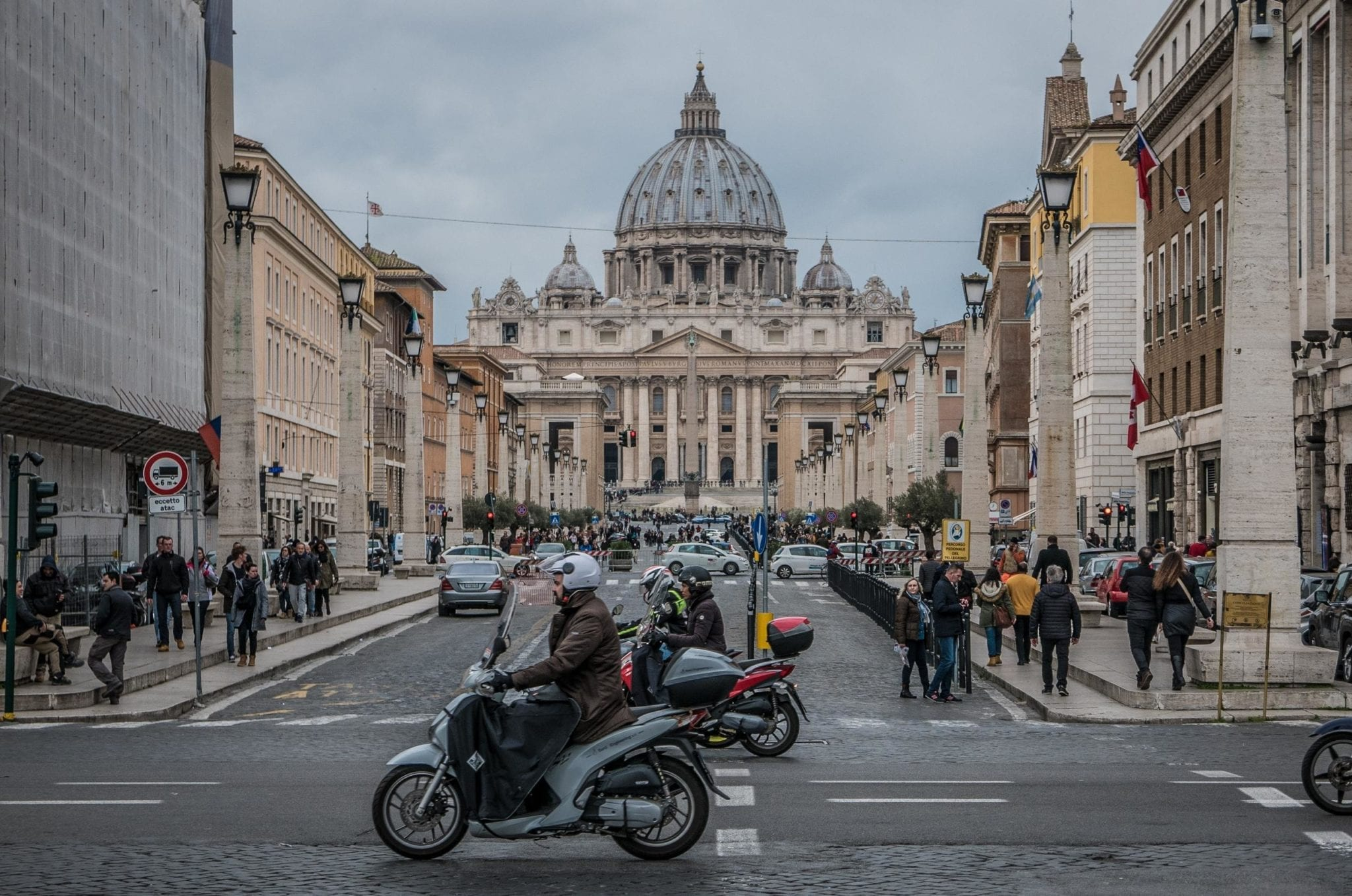 A street view of Rome with a man on a motorbike in front of the large dome of St. Peter's Basilica.