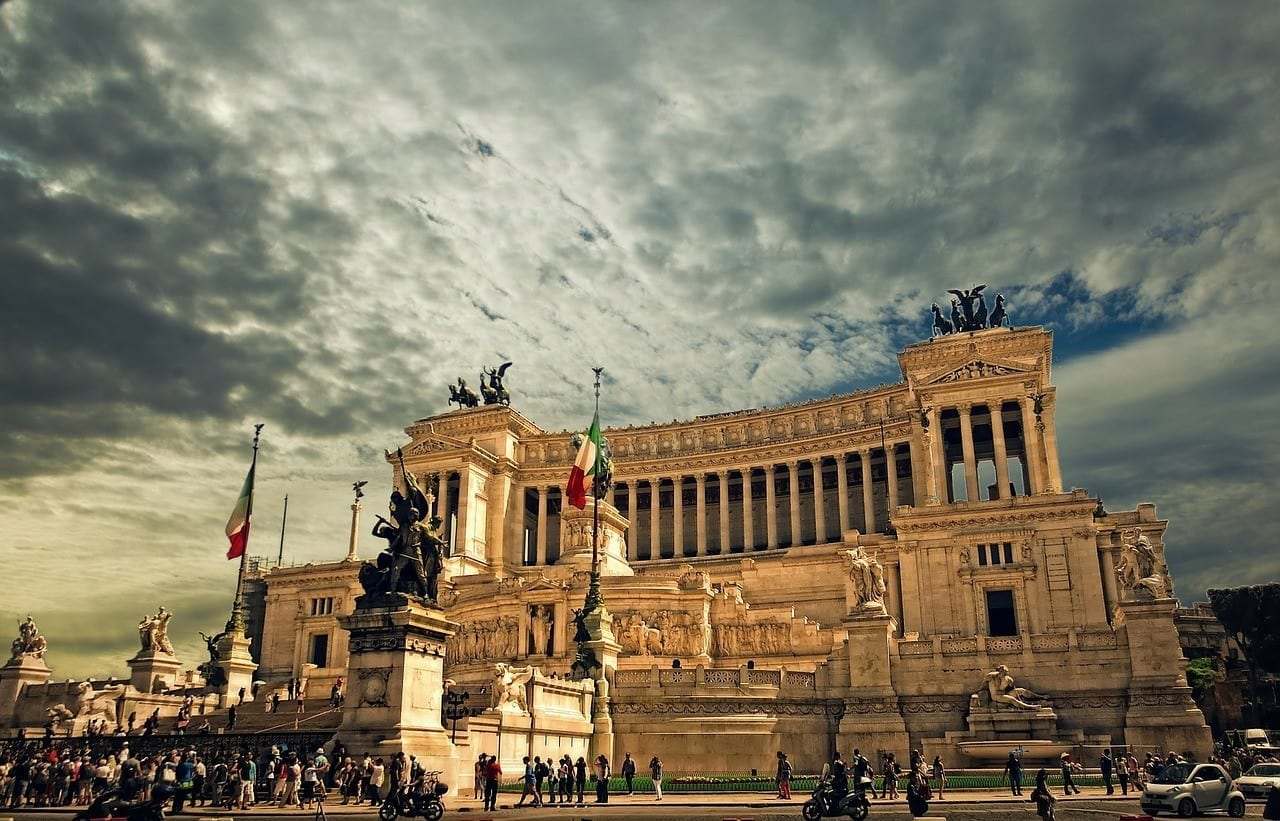 """Vittorio Emanuele, the """"wedding cake"""" building of Rome with large columns and Italian flags flying, bright yellow at dusk beneath a cloudy sky."""