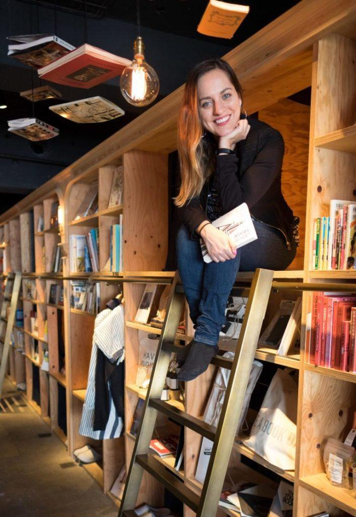 Kate sits at the top of a ladder amongst bookshelves that double as dorm beds at the Tokyo Book and Bed Hostel.