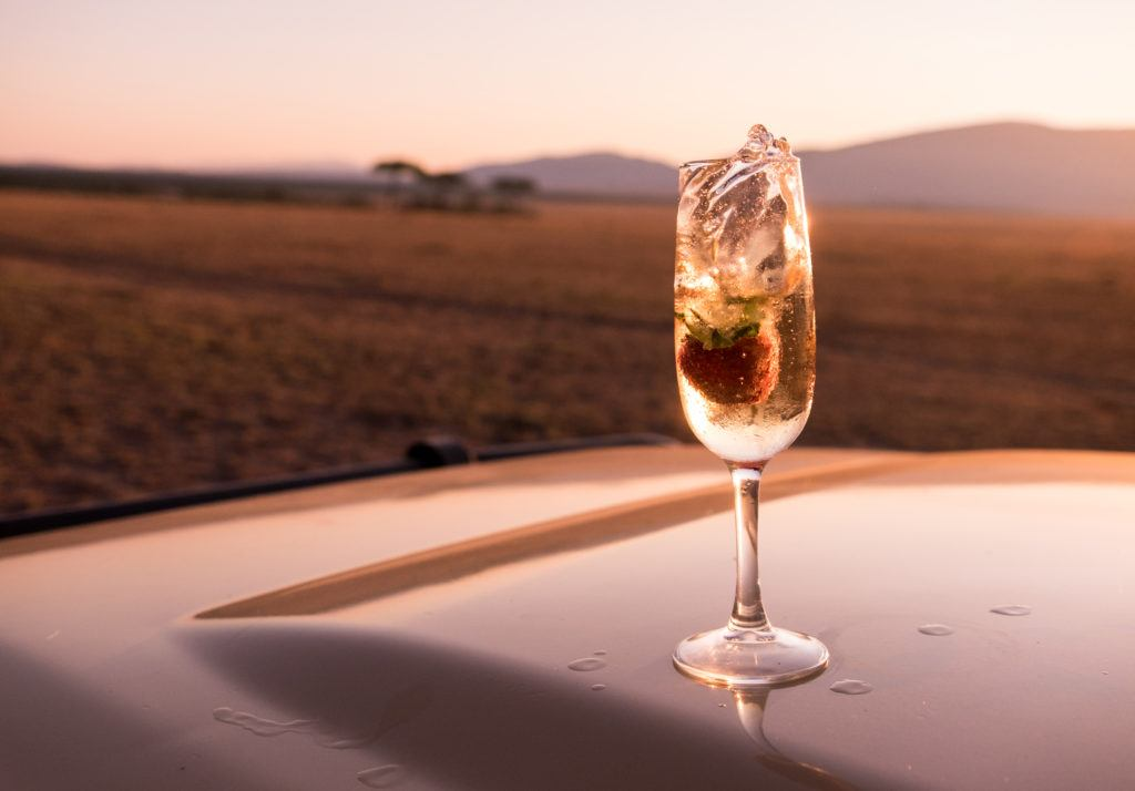 A strawberry slowly dropping into a glass of champagne at sunrise.