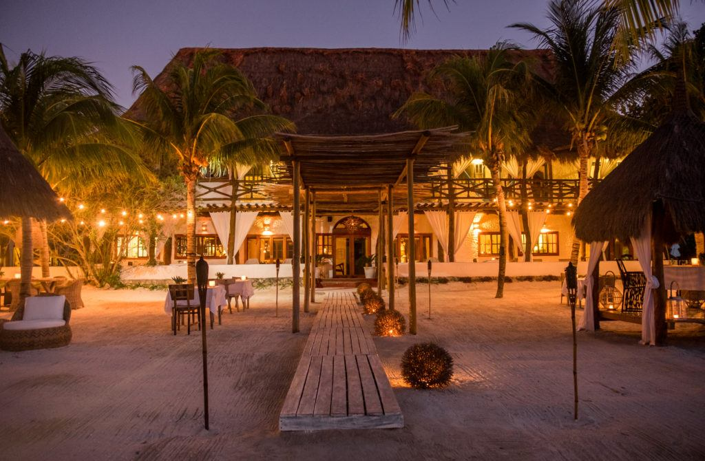 Casa Sandra, with its white walls and thatched roof, lit up at night