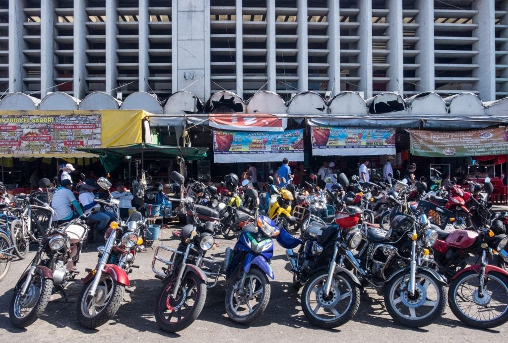 Motorcycles lined up in a row, parked outside a building in Merida, Mexico.