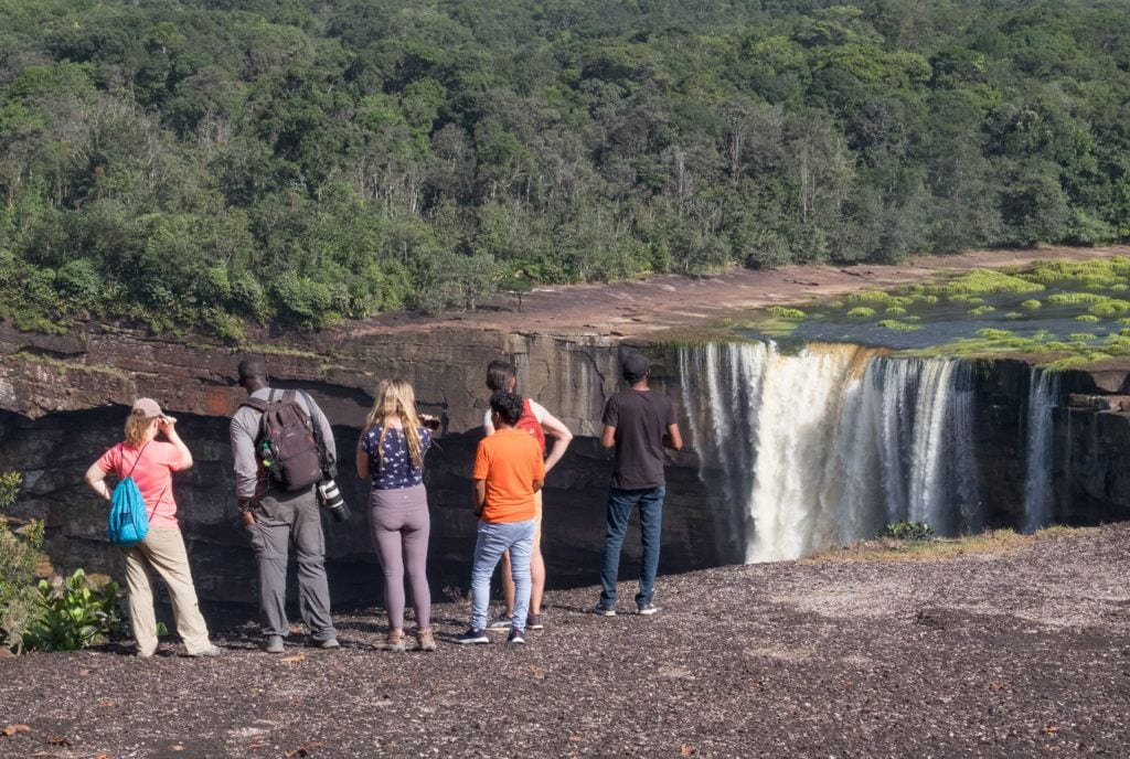 Four backpackers standing on the edge facing Kaieteur Falls in Guyana, no safety rail whatsoever!