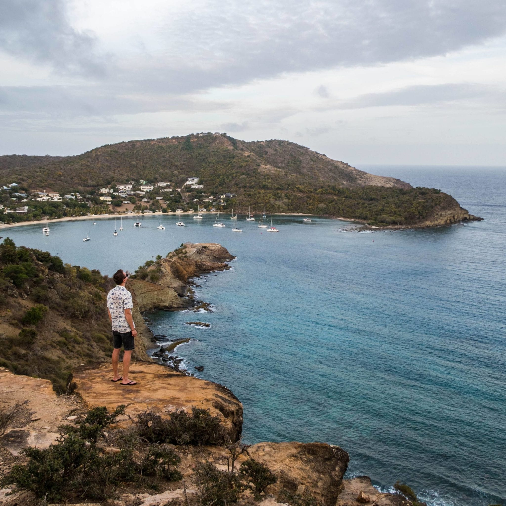 Patrick standing on the edge of a cliff, looking on to the English Harbour in Antigua.