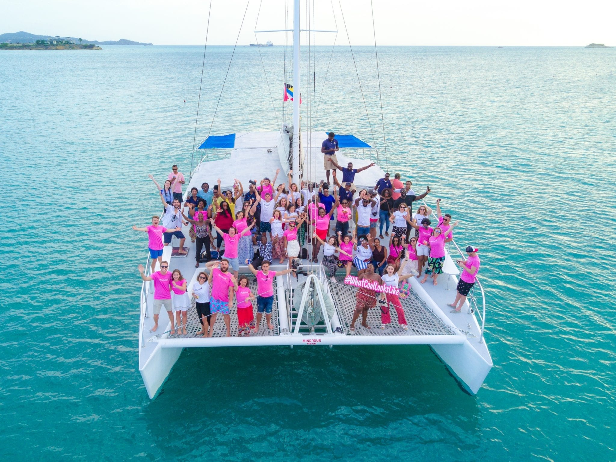 In a drone shot, a few dozen people, some wearing bright pink t-shirts, pose with their arms in the air on a large catamaran in Antigua. The sea surrounding them is turquoise.