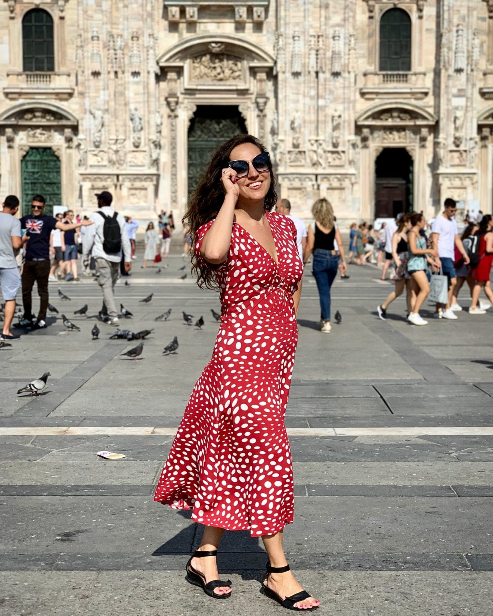 Kate wears a long red short-sleeved dress covered with white polka dots of various sizes and black sandals. She wears black sunglasses and poses as if about to take them off with one hand. She is standing in front of Milan's Duomo and in the background you can see pigeons and people taking pictures in front of it.