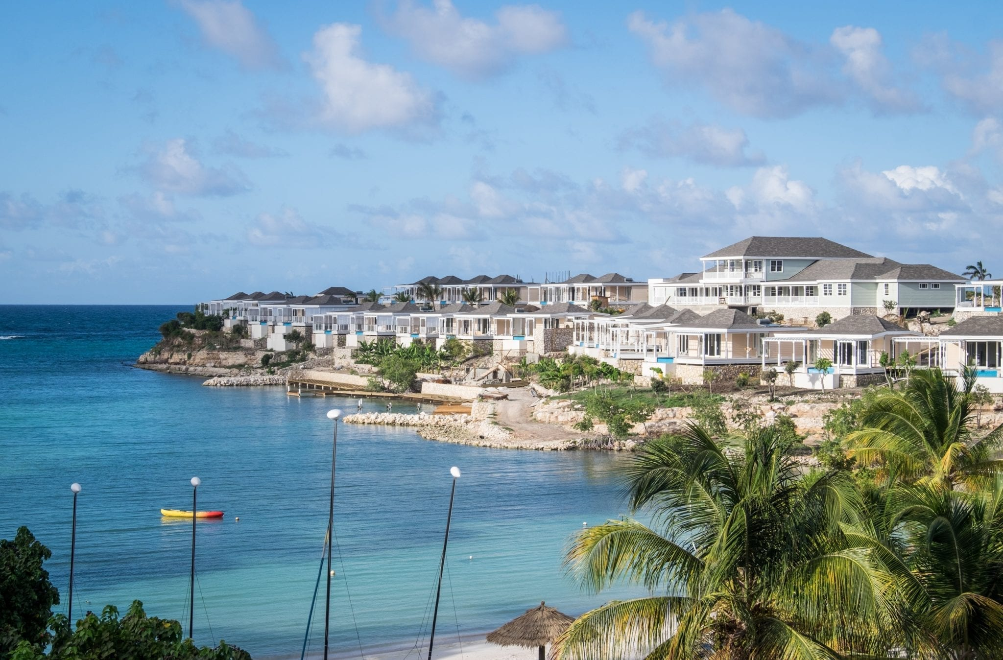 A view over the turquoise Caribbean Sea with white hotel rooms on a piece of rocky land to the right. There are palm trees in one corner.