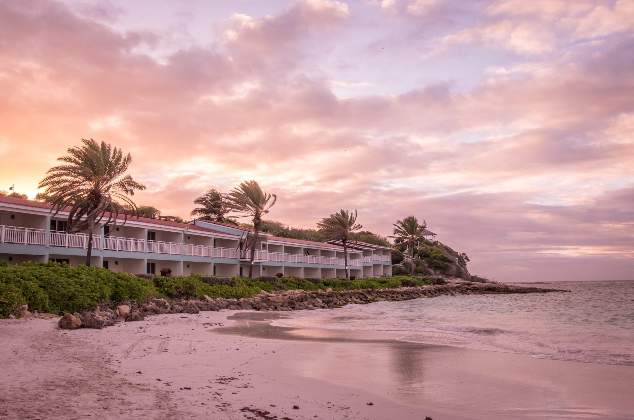 A pink sunset over a beach with white hotel rooms and palm trees in the background.