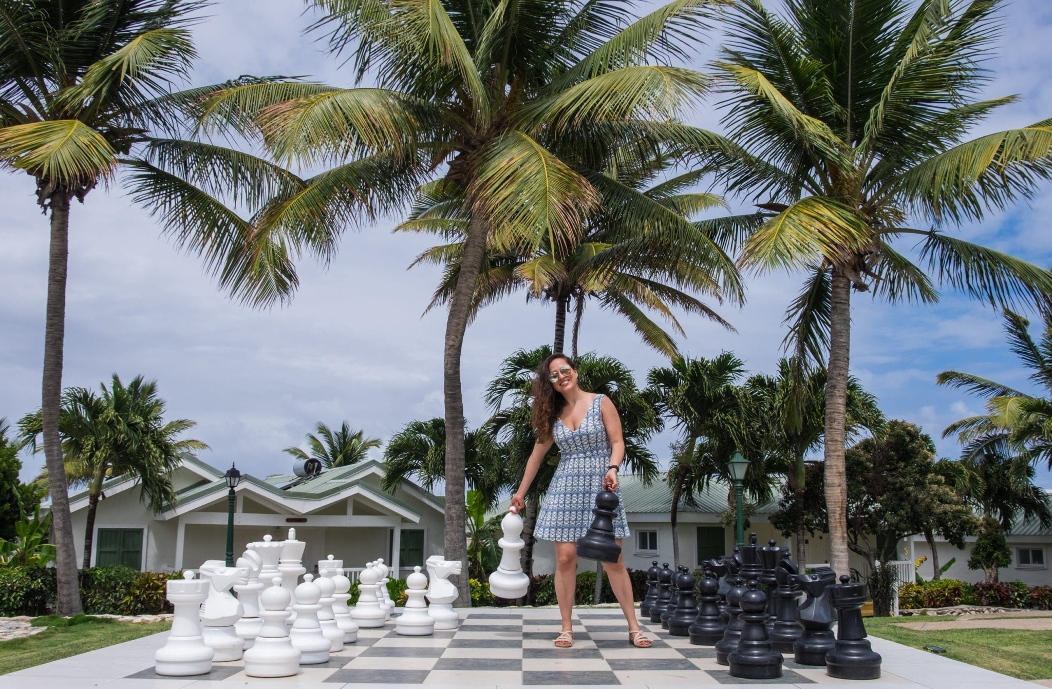 Kate plays on a giant chess board in Antigua, holding a white bishop in one hand and a black pawn in another. She is wearing a short green and white patterned dress. Above her are palm trees and a blue and white streaky sky.