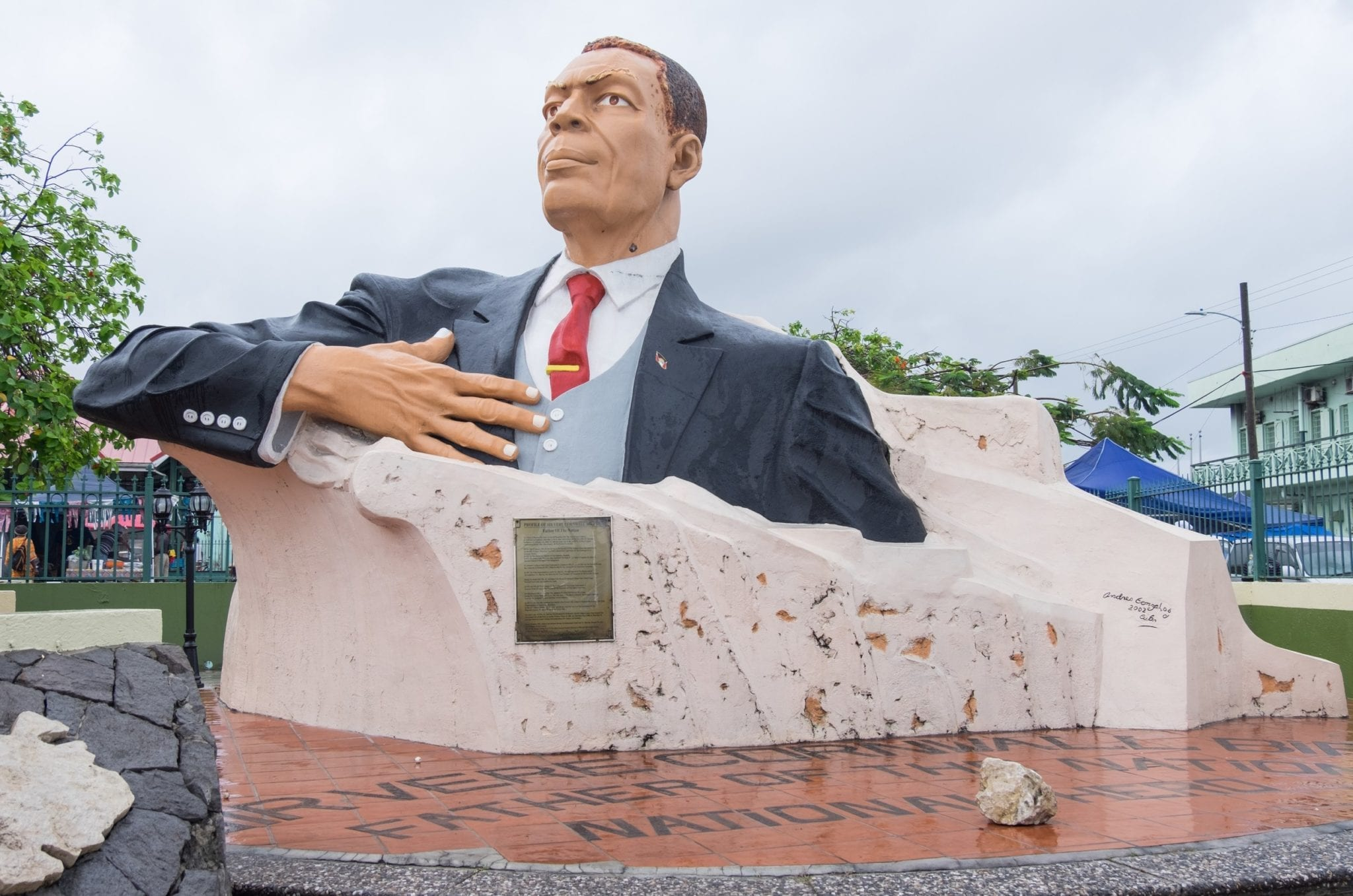 Giant colored of the first president of Antigua, from the chest up in a suit coming out of a piece of rock in the center of town