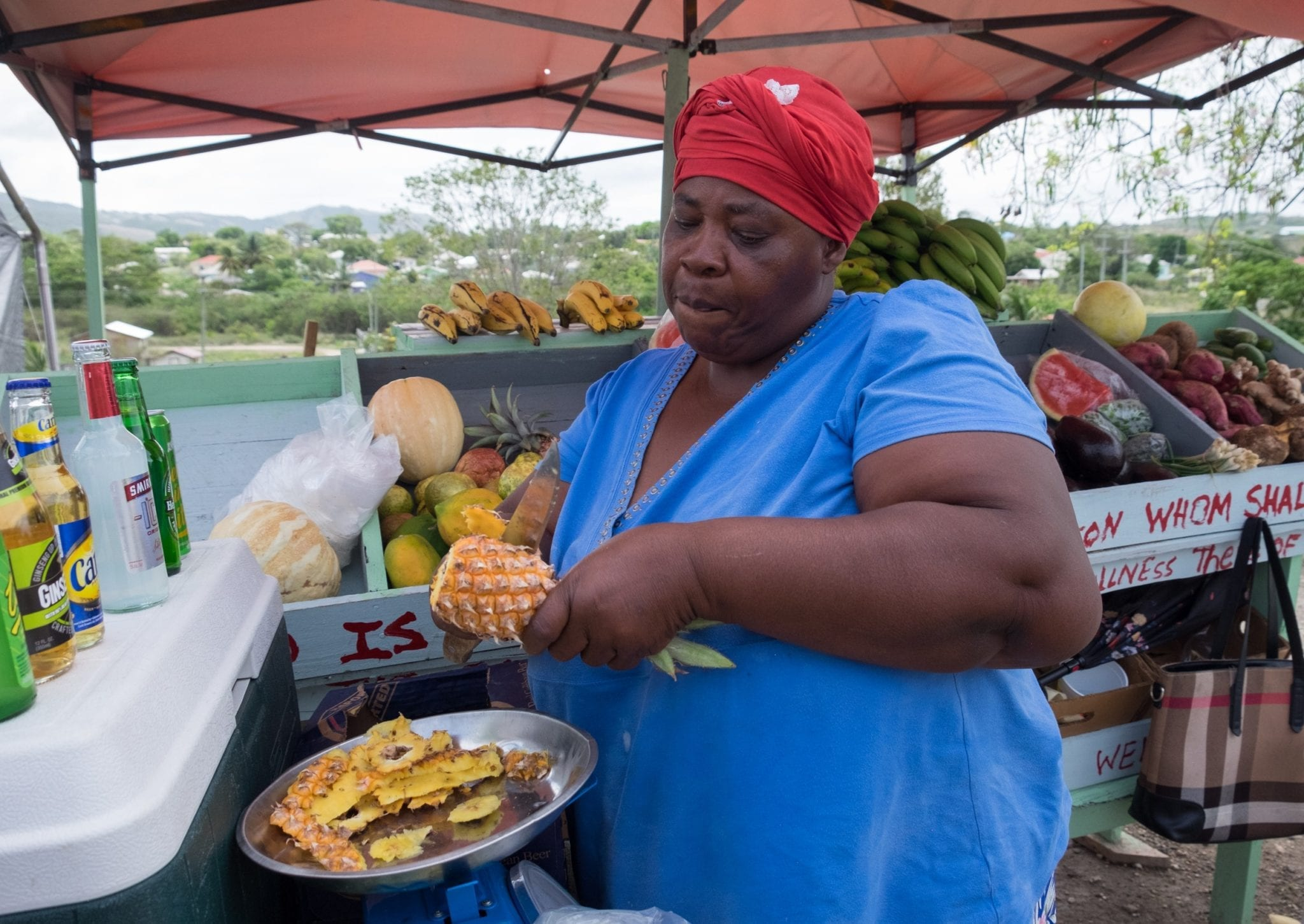 A woman in a red bandana slices a pineapple into a plastic bag in Antigua.