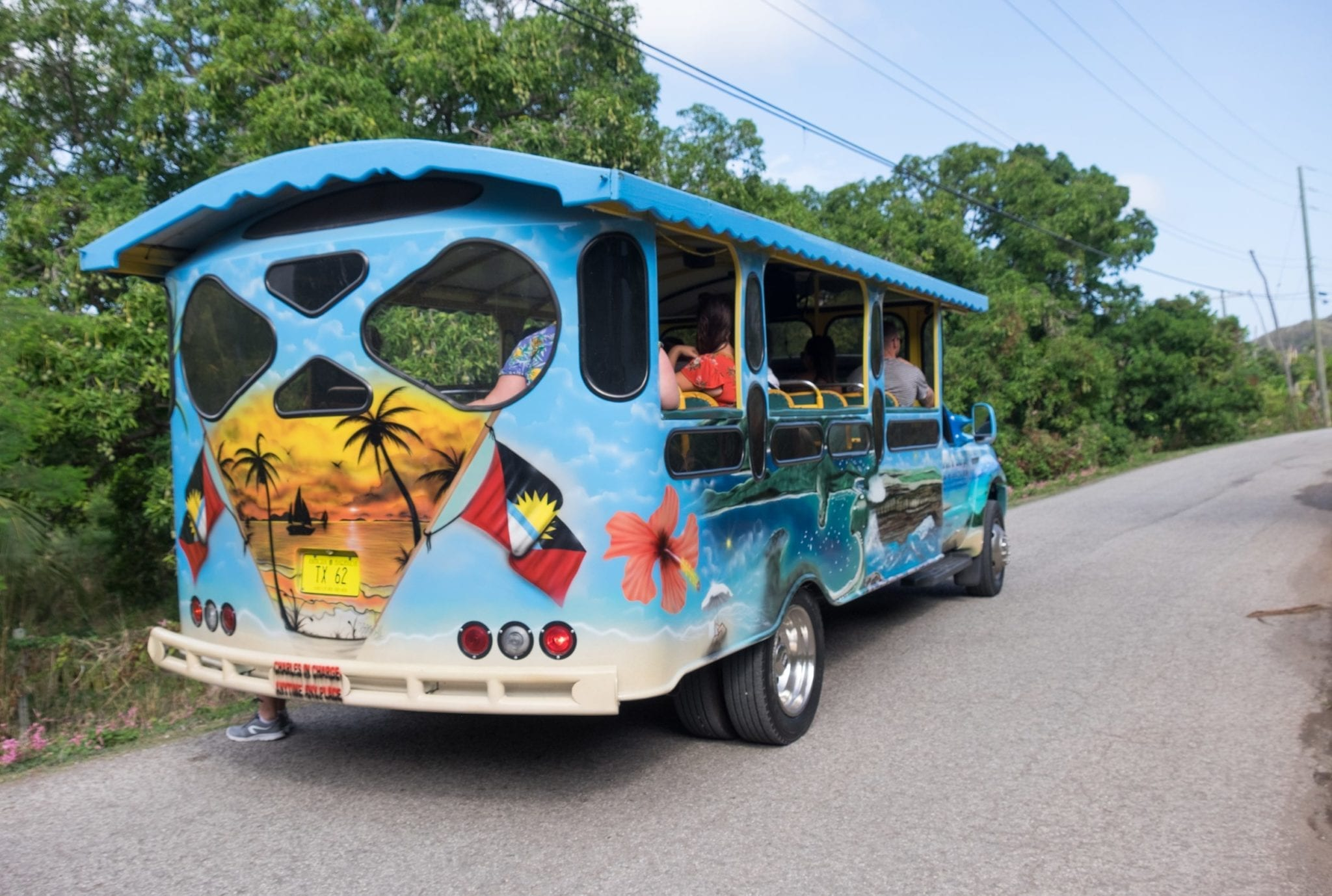 The back of a brightly painted blue bus with orange palm trees painted on the back in Antigua