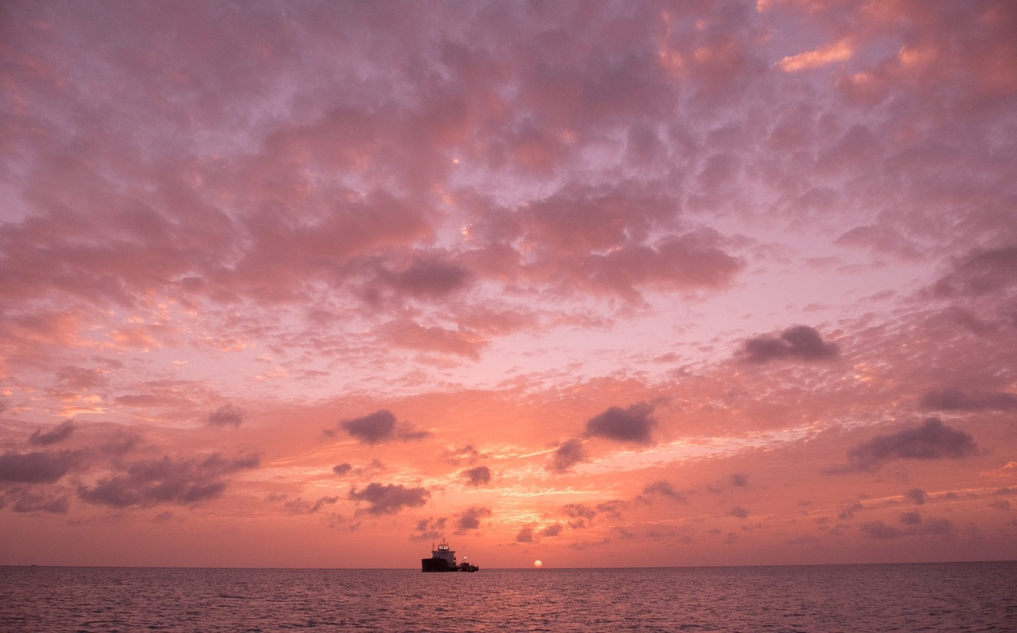 A pink sunset with lots of fluffy purple clouds in Antigua. At the bottom is the sea, a black silhouette of a boat, and a tiny yellow sun.
