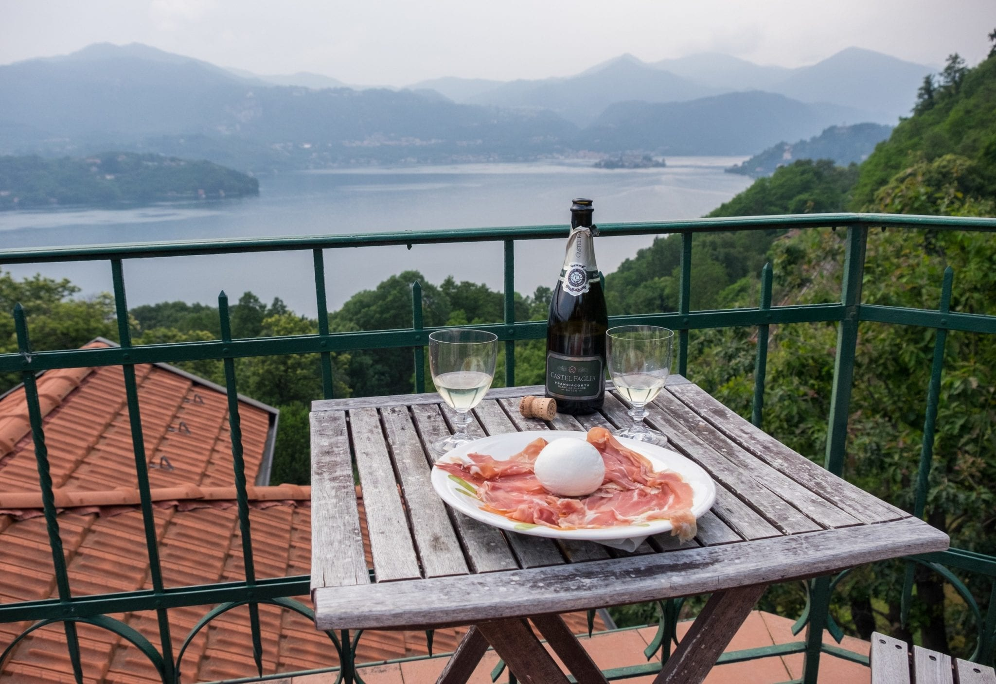 A terrace overlooks a blue and gray misty Lake Orta in the distance, mountains rising up over the lake. In the foreground there is a weathered wooden table. On it is a plate covered with prosciutto and a ball of burrata cheese; behind it are a bottle of Franciacorta sparkling white wine and two goblets filled with the wine.