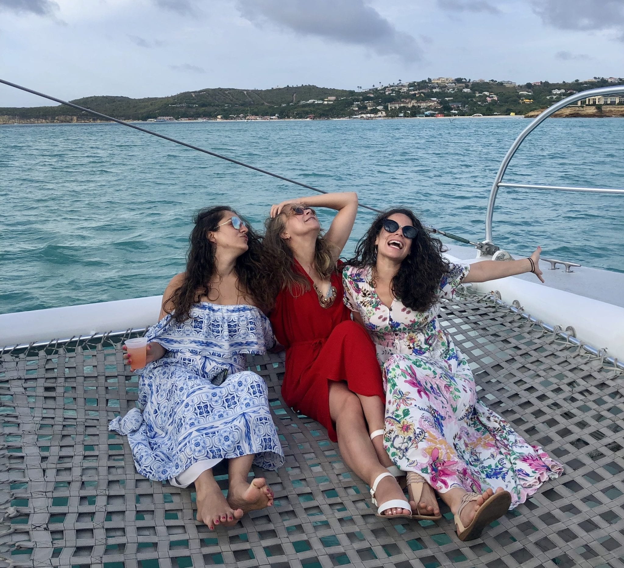 Three girls in floral patterned dresses sitting on the net of the catamaran, looking off to the side and making goofy kissy faces.