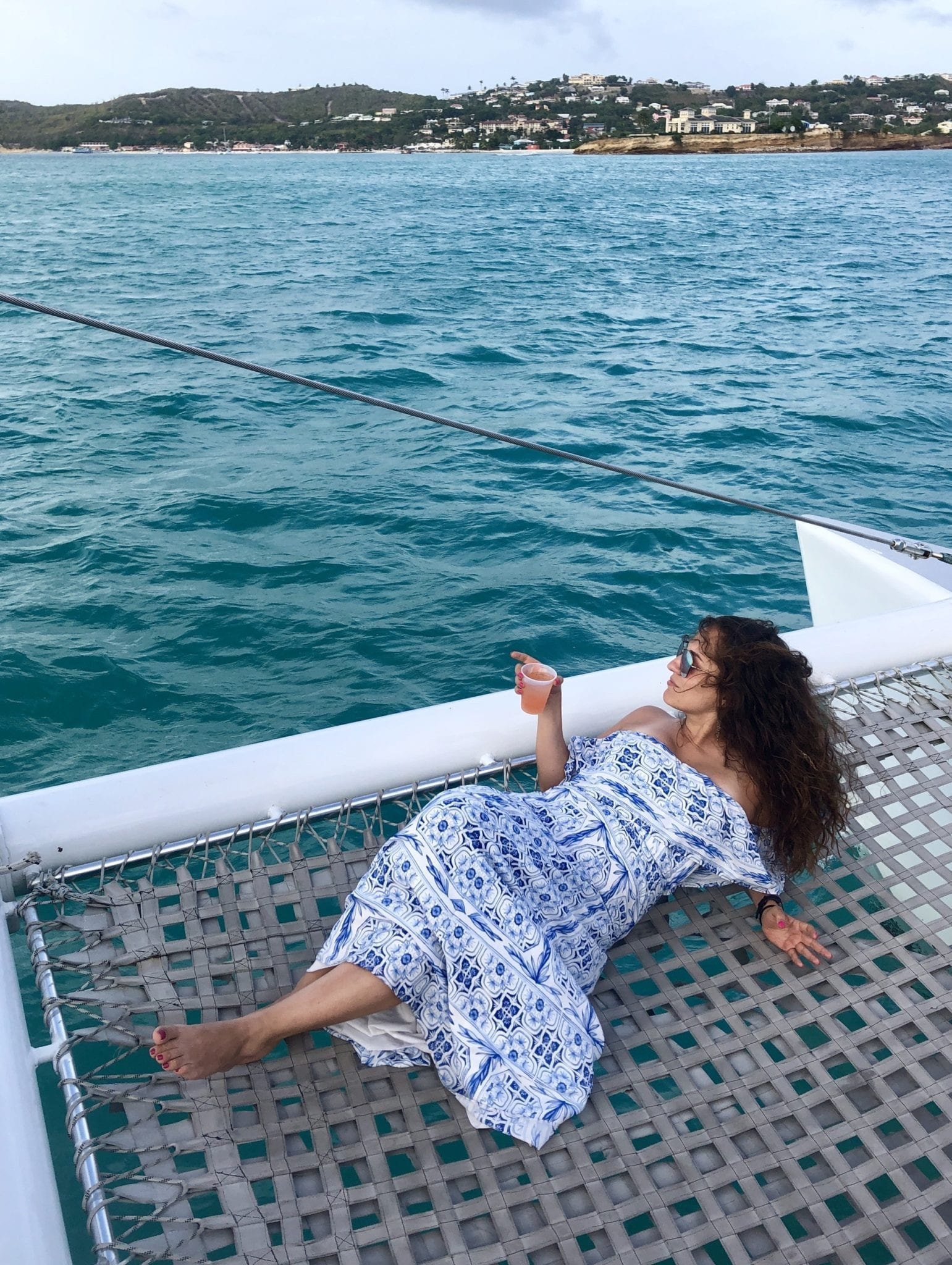 Kate lying down on a net on the end of a catamaran, wearing an off the shoulder white and blue patterned dress, hair long and curly, leaning on her elbows, holding a plastic cup of rum punch in one hand, and staring off into the distance -- turquoise sea and green land in the distance.