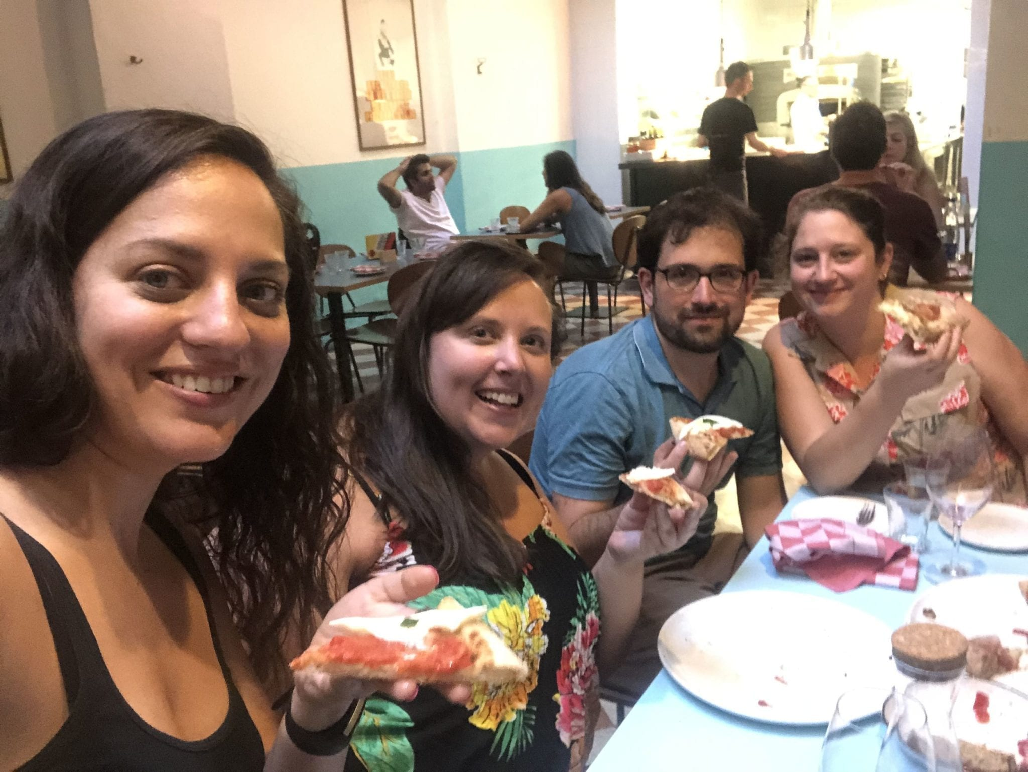Kate and her friends Cailin, Mike, and Steph pose for a selfie at a pizzeria in Bologna, each holding up a slice of pizza.