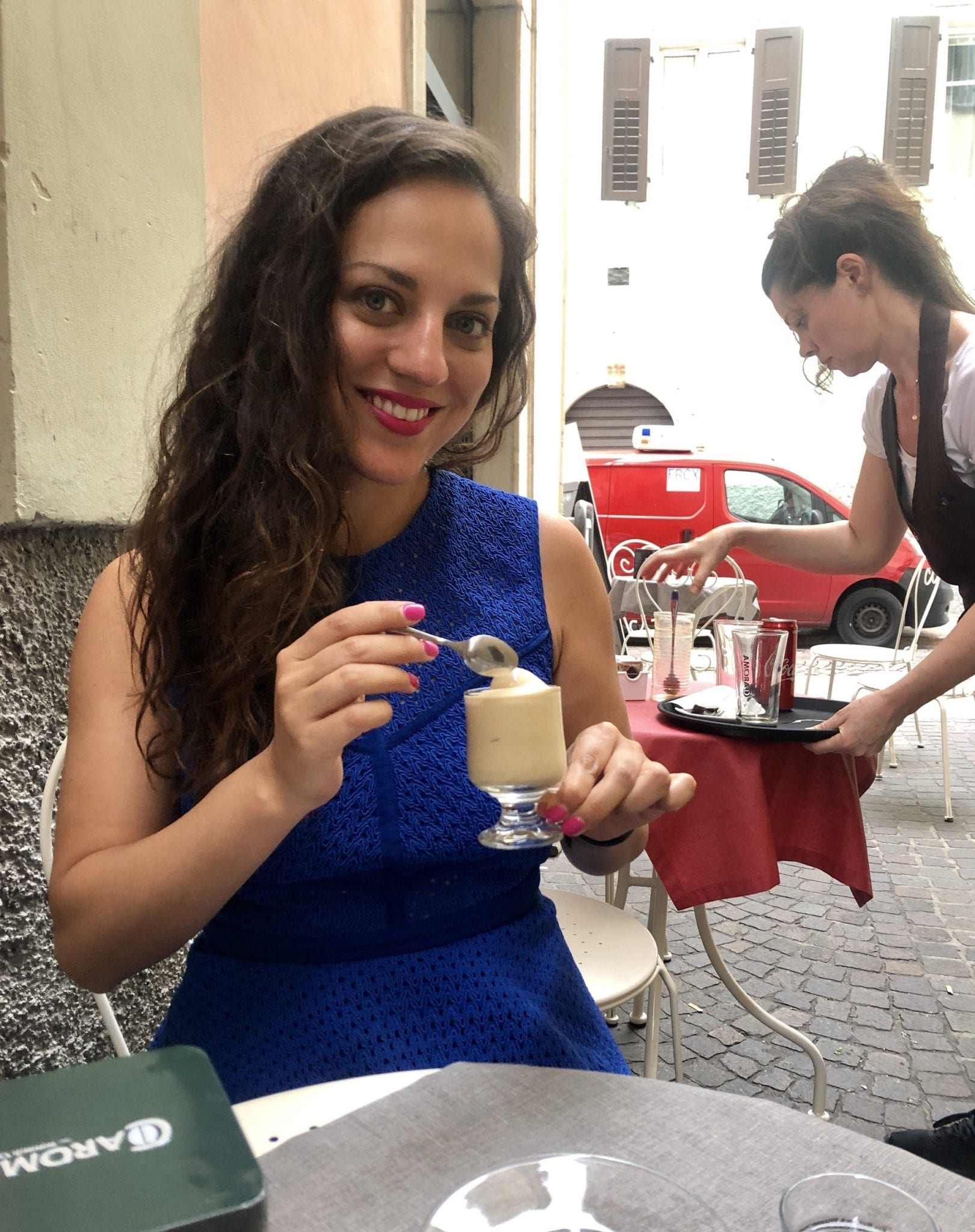 Kate wears a royal blue Pinko dress that goes up to her neck and has a transparent lacy fabric. Her hair is down a curly and she holds a cafe crema (soft serve espresso) in her hand. She is sitting at a sidewalk cafe in Trento.