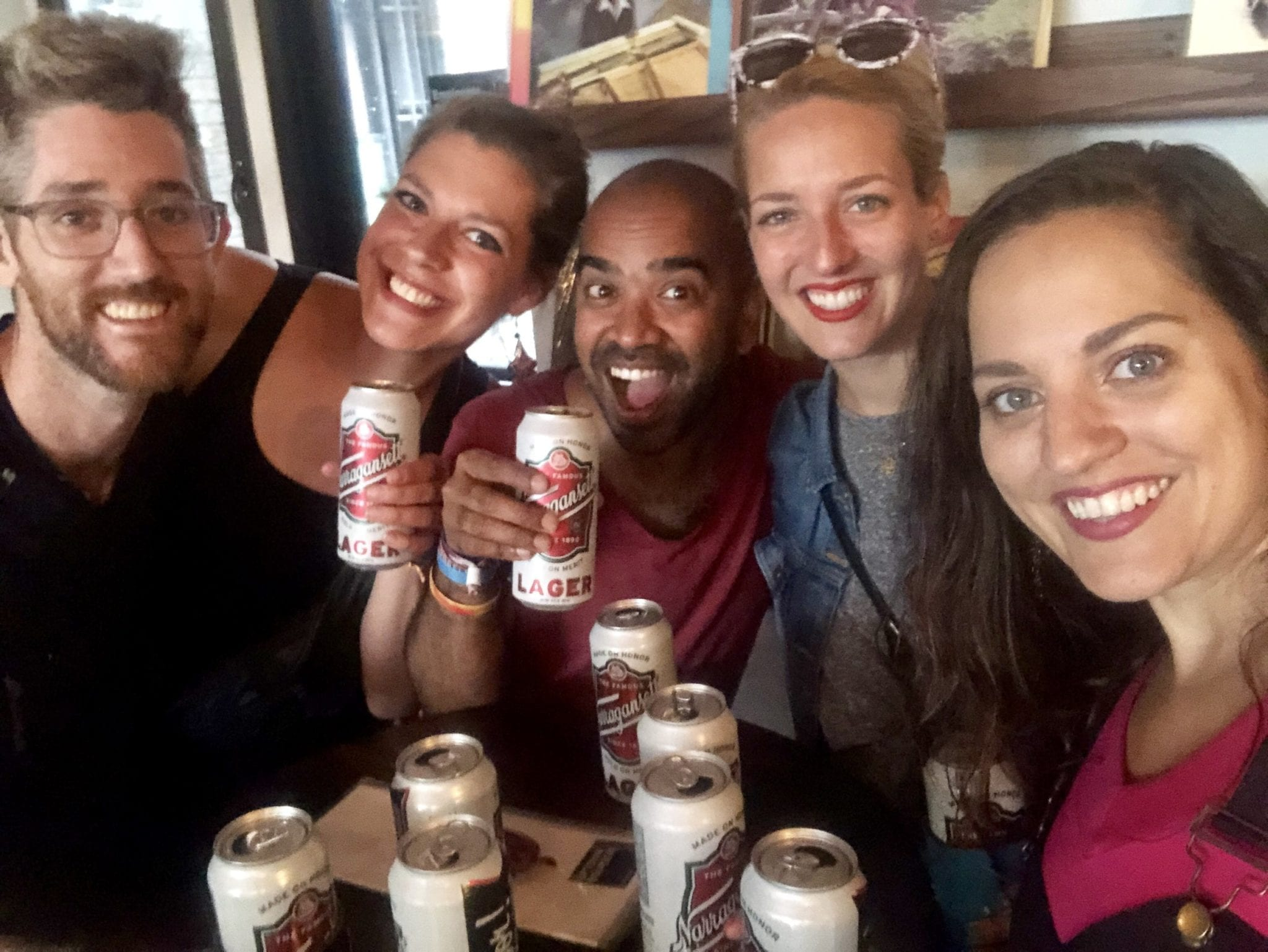 Group selfie: Kate with her friends Sabrina and Kash, her sister Sarah, and her sister's partner Matt, all around a bar table topped with twelve Narraganset tallboy beers.