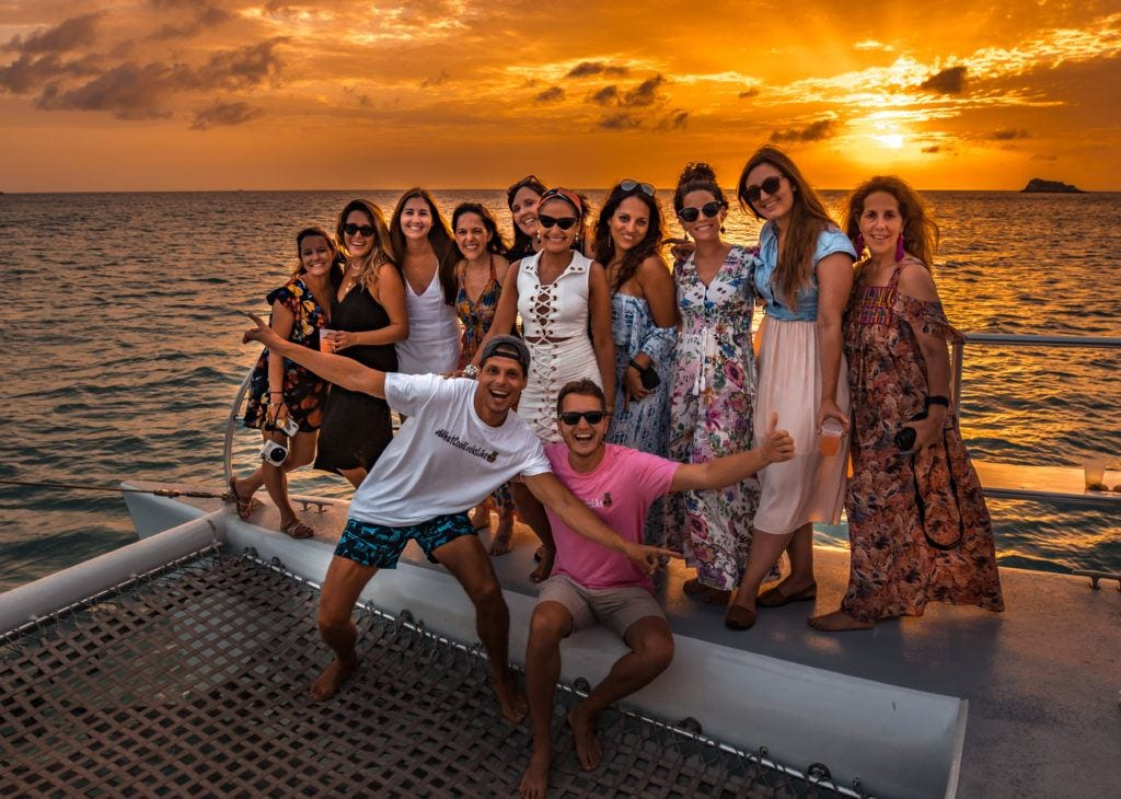 A group of friends posing on a catamaran with a bright orange sunset behind them.