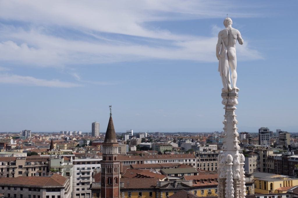 View from Milan's Duomo: A nude statue looks over the city from behind; the city is a mix of old Renaissance towers and modern buildings underneath a periwinkle blue and white striped sky.