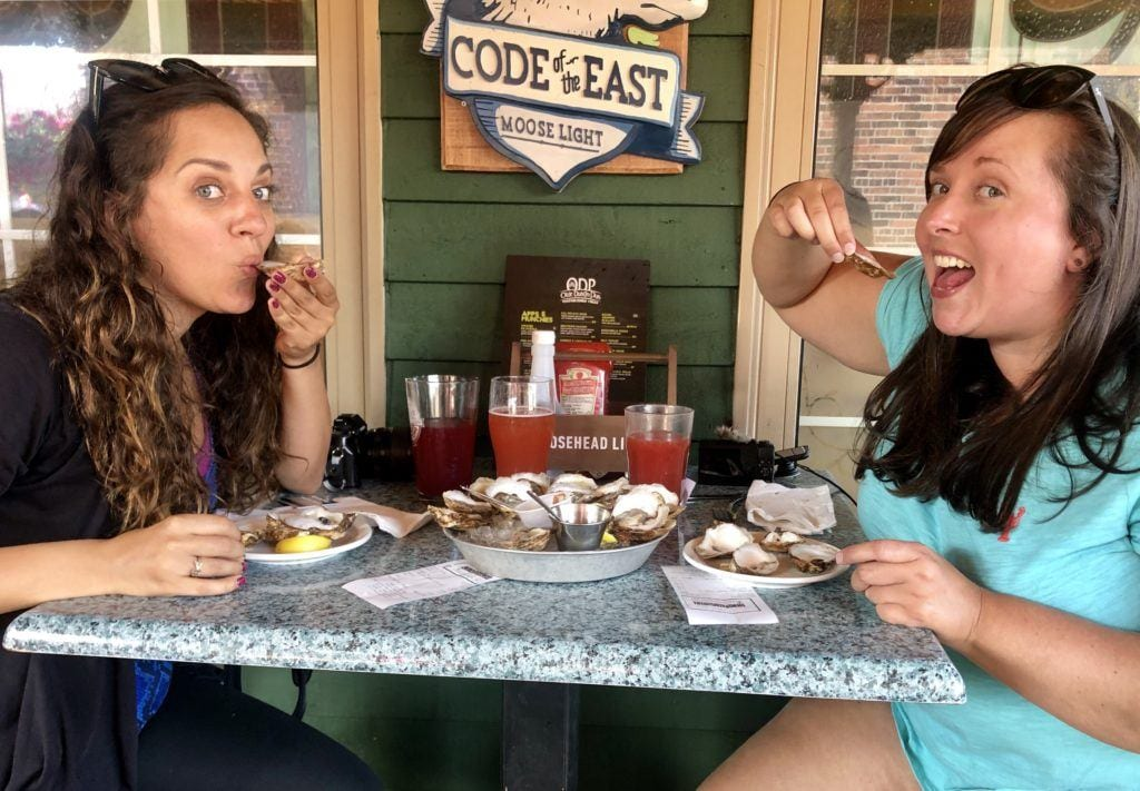 Kate and Cailin pause while eating a plate of 24 oysters at an Irish bar in PEI