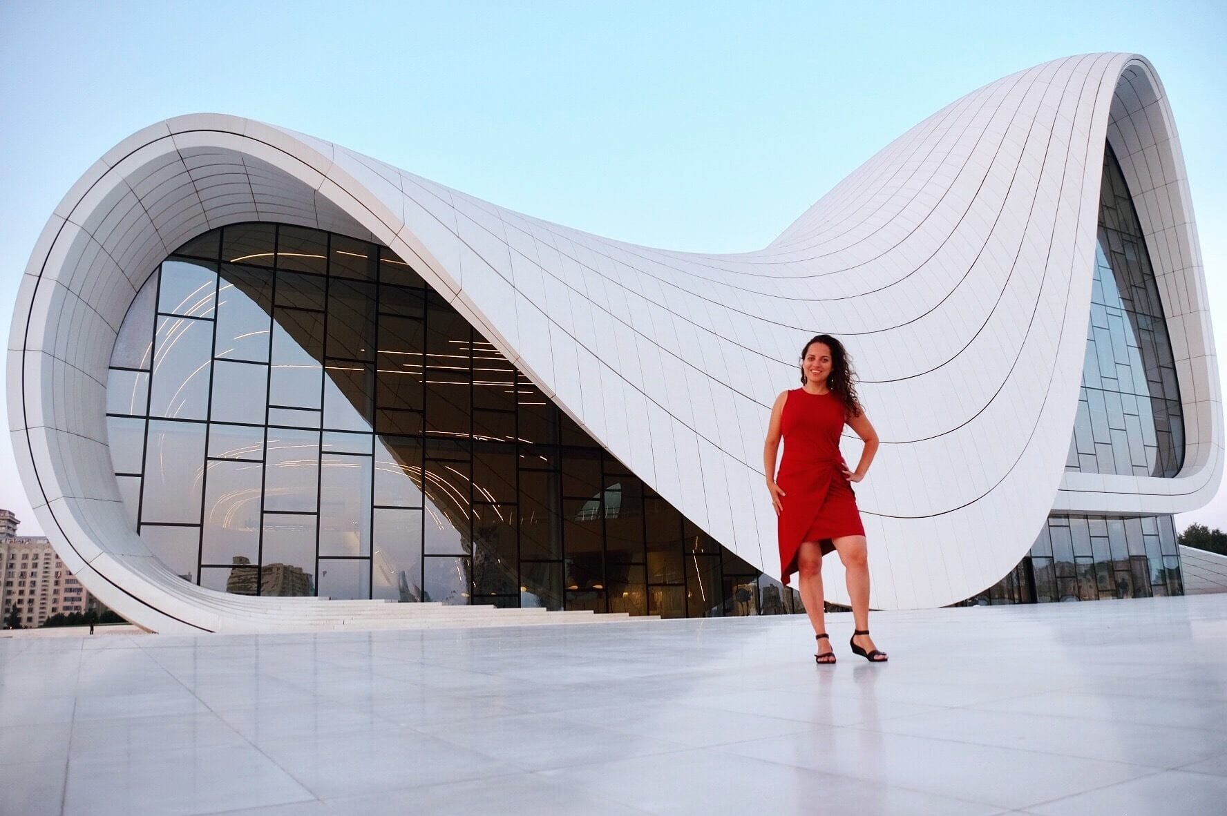 Kate stands in front of a modern building shaped like a sideways S, standing in a red dress.