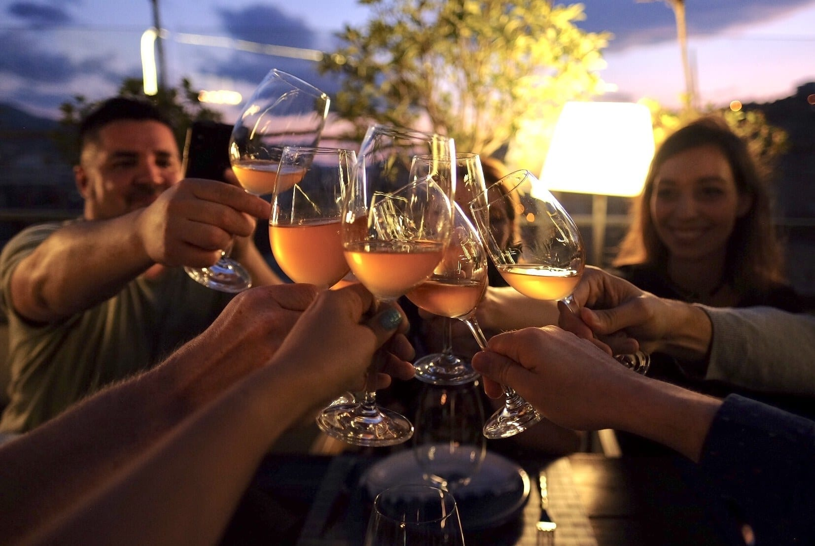 Several people toasting glasses of orange wine on a darkened rooftop at sunset.