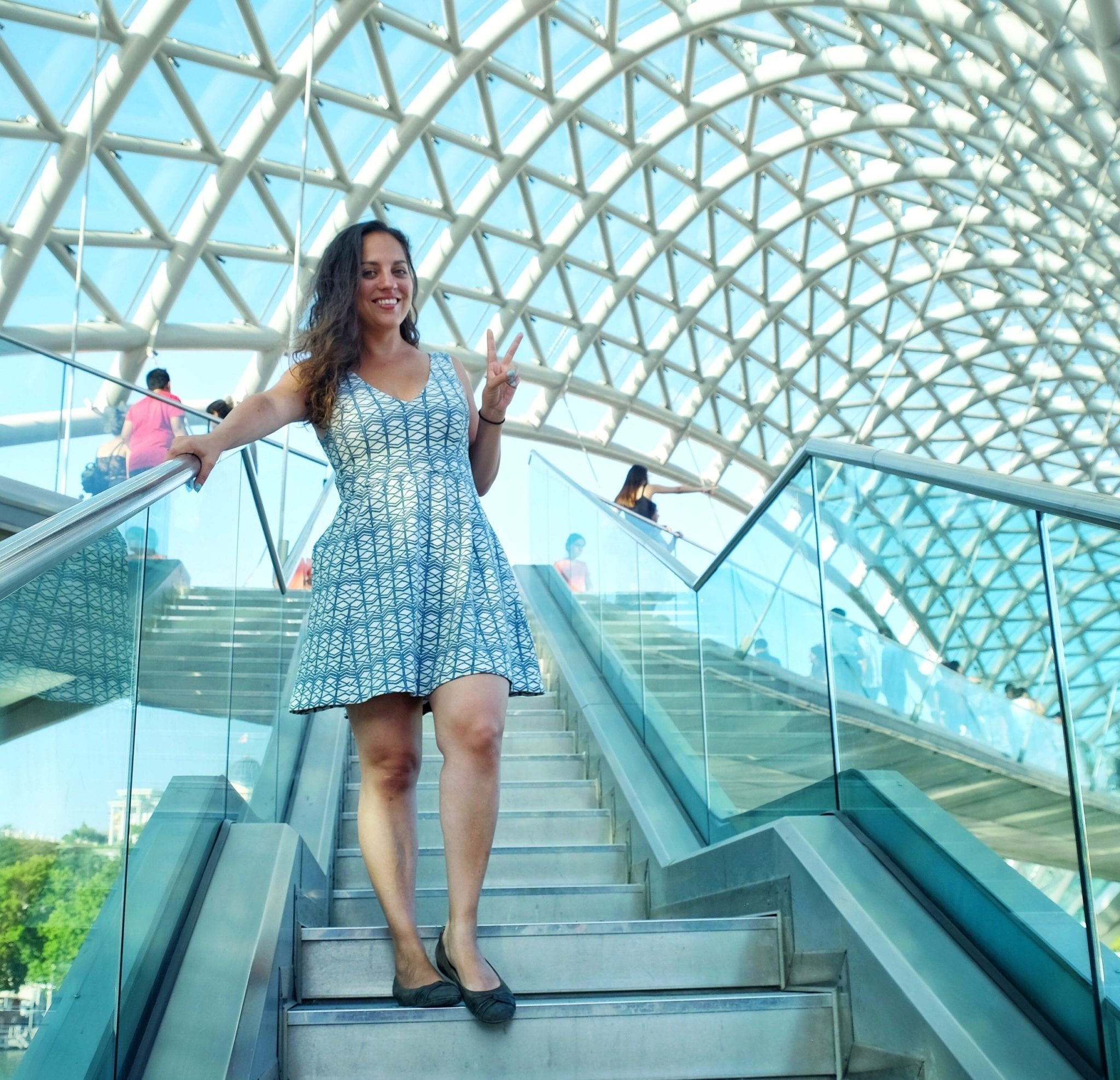 Kate stands underneath the green-and-white-patterned Peace Bridge in Tbilisi, Georgia, giving a peace sign and wearing a dress that has a very similar green and white geometric pattern.