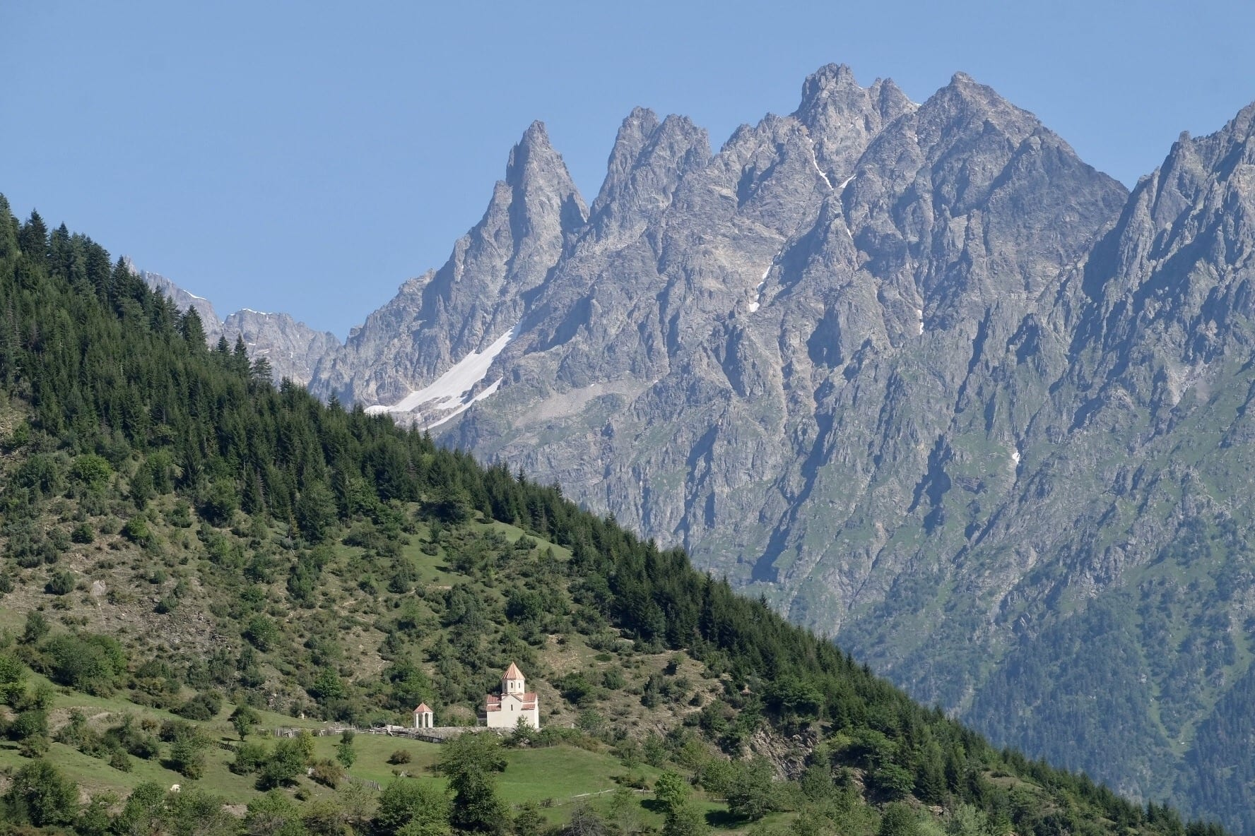Two mountains: a green one with a tiny white church perched on it, in front of a taller, jagged gray mountain in Svaneti, Georgia.