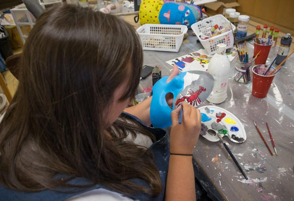 Cailin paints a lobster on her mask at the Mi-Careme Centre