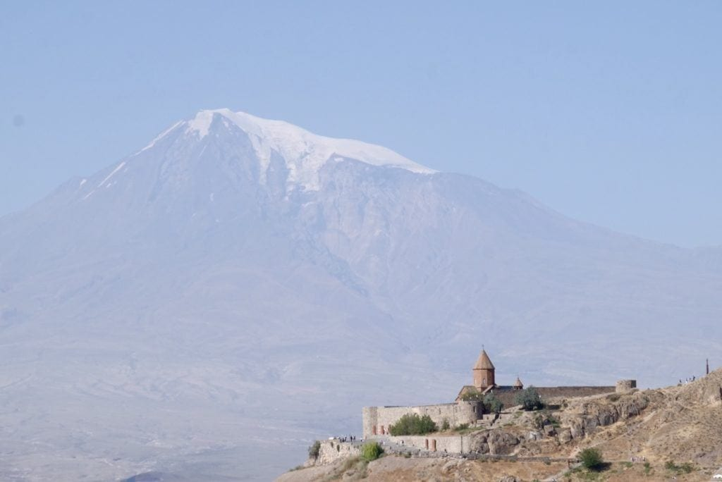 In the bottom right corner, Noravank monastery; in the rest of the background, a hazy blue view of Mount Ararat.