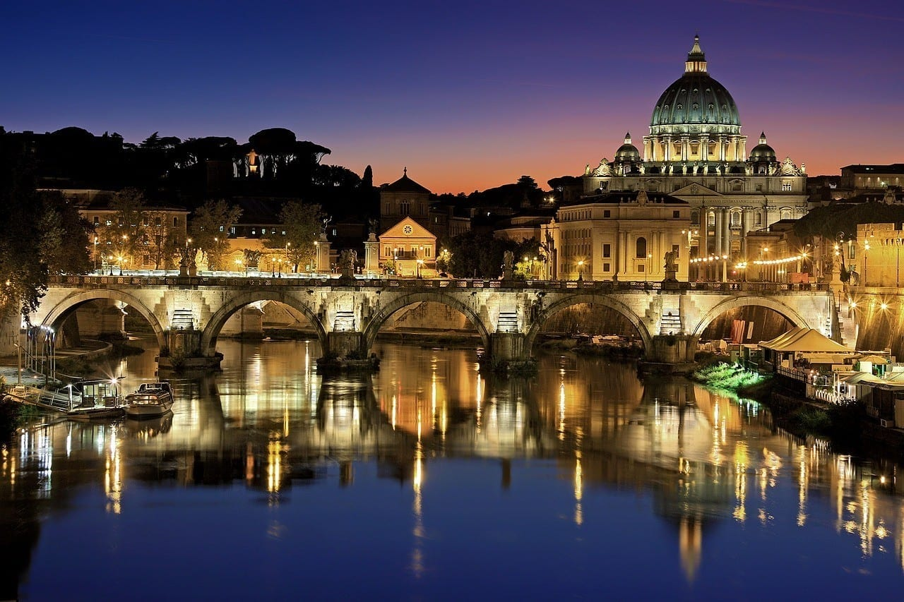 A purple and pink sunset in Rome. You see the lights of a bridge reflecting in the river, and on the right is the dome of St. Peter's Basilica.