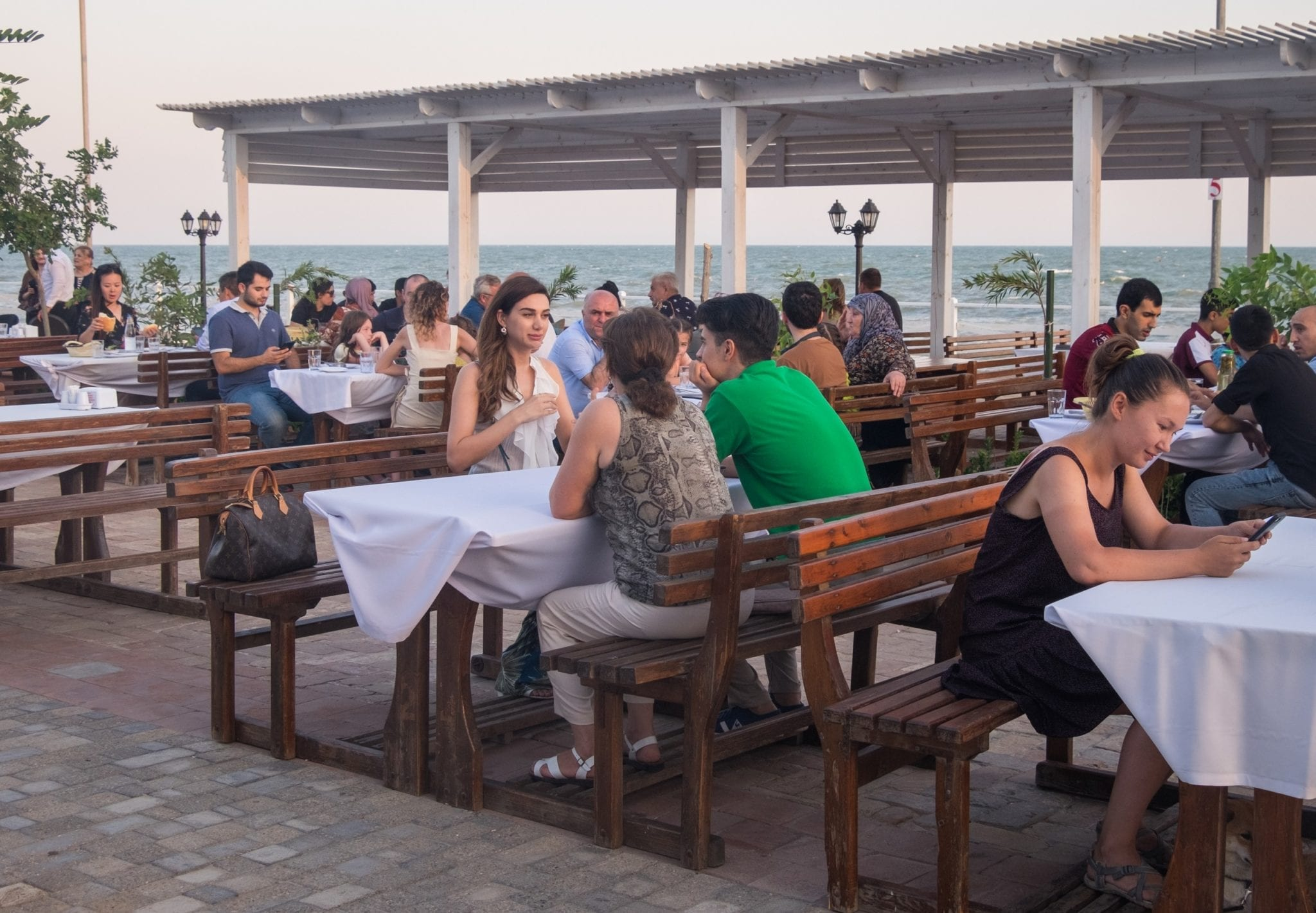 People sitting at outdoor tables at a restaurant on the Caspian Sea.