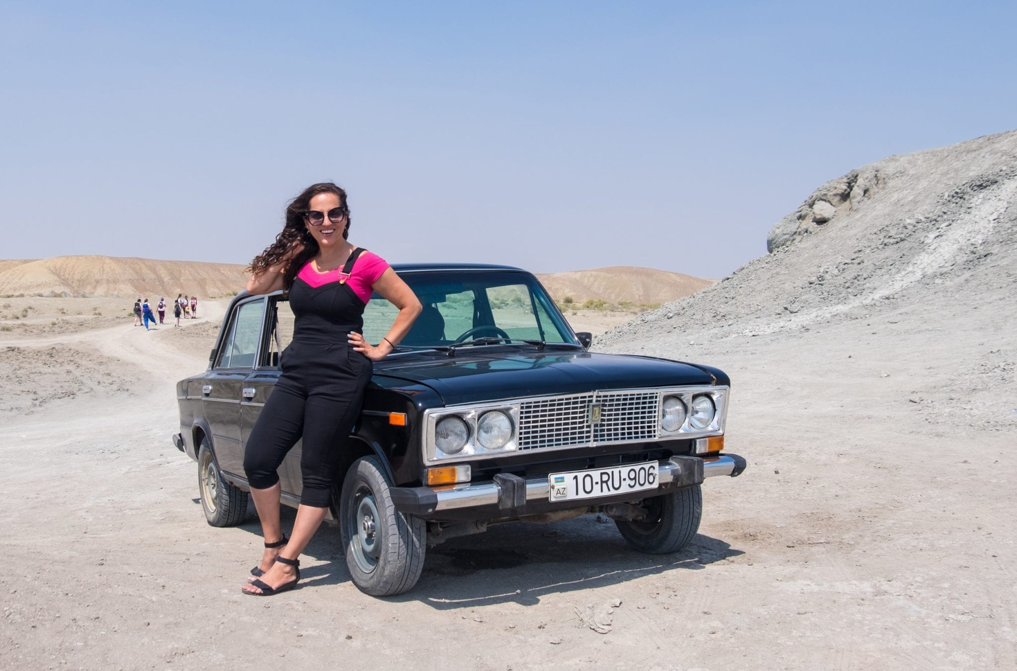Kate wears overalls and a pink shirt and poses with her hand behind her neck while sitting on a Soviet-era Russian Lada car. She's in the middle of the gray-brown dessert beneath a pale blue sky.