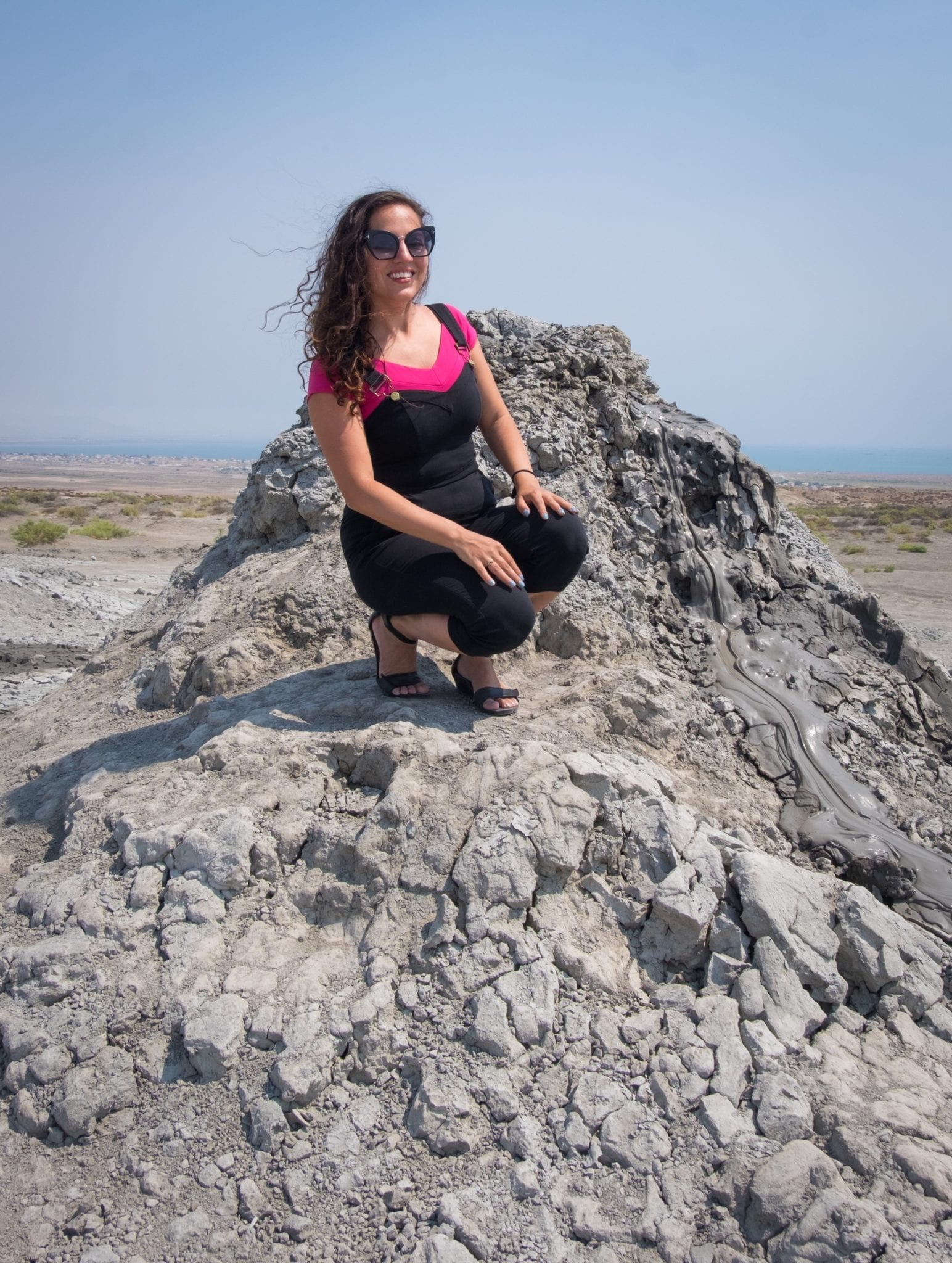 Kate crouches near the edge of a gray bubbling mud volcano.