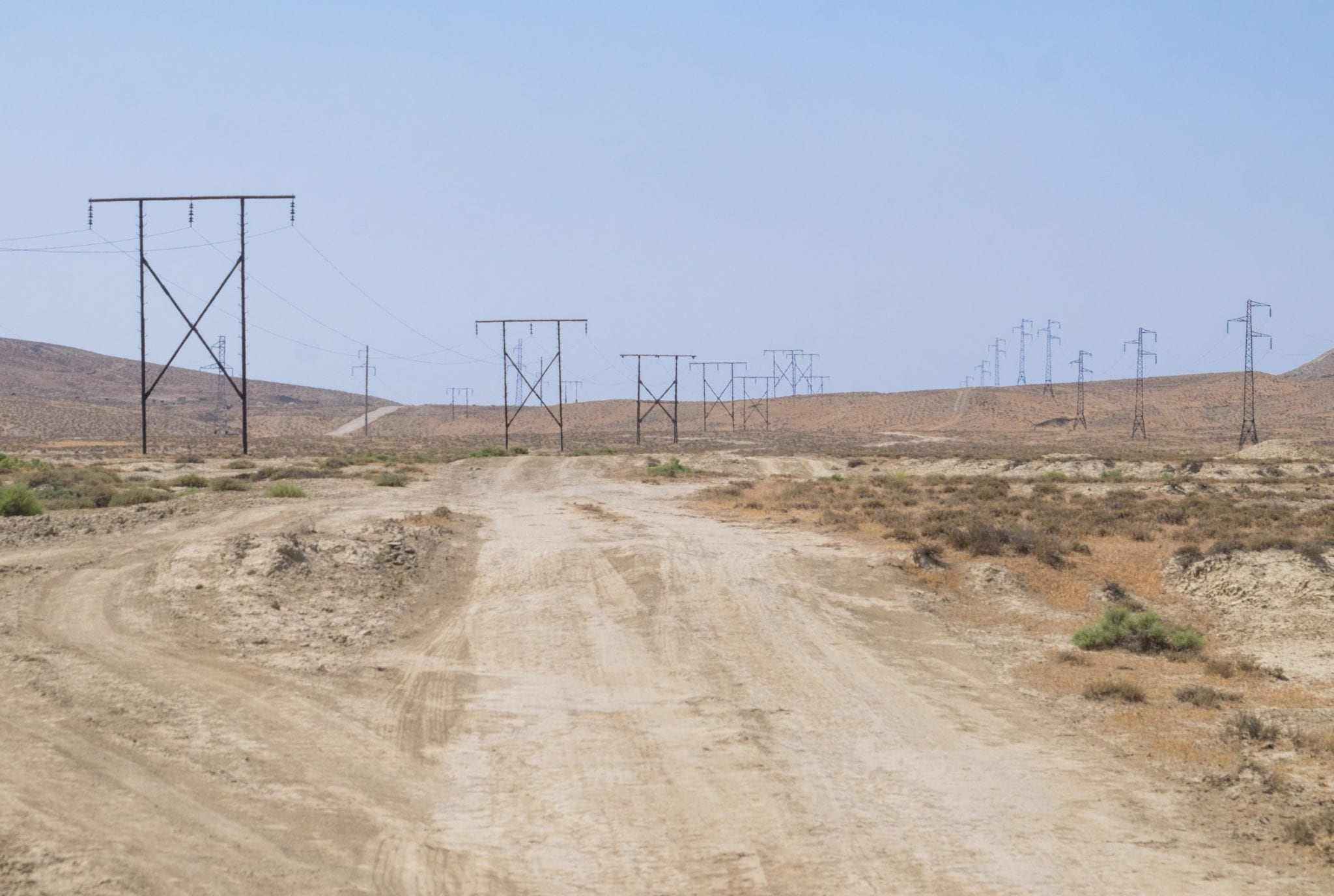 A rough desert landscape with telephone poles running across the sand.