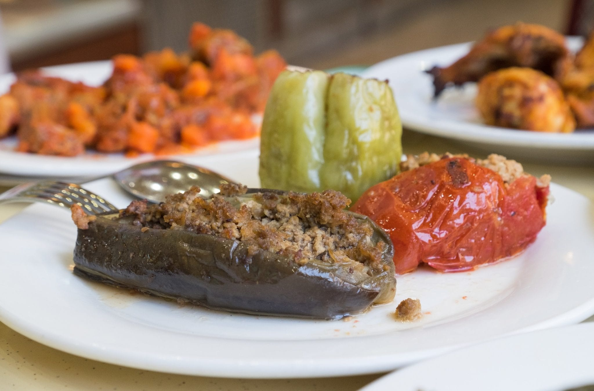 On a plate, an eggplant and two kinds of peppers stuffed with minced beef.