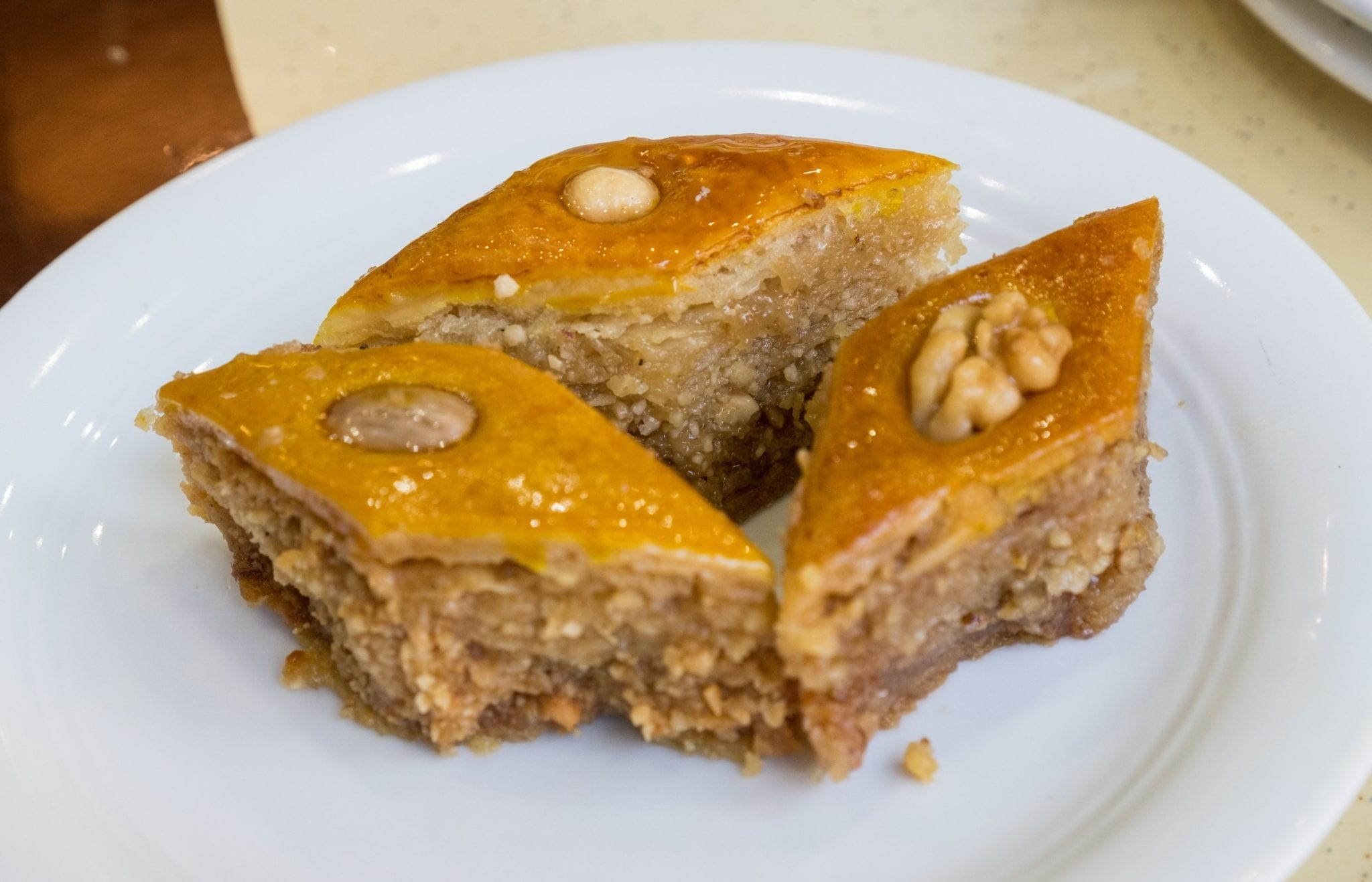 Three pieces of baklava, one topped with an almond, one with a walnut, one with a hazelnut.