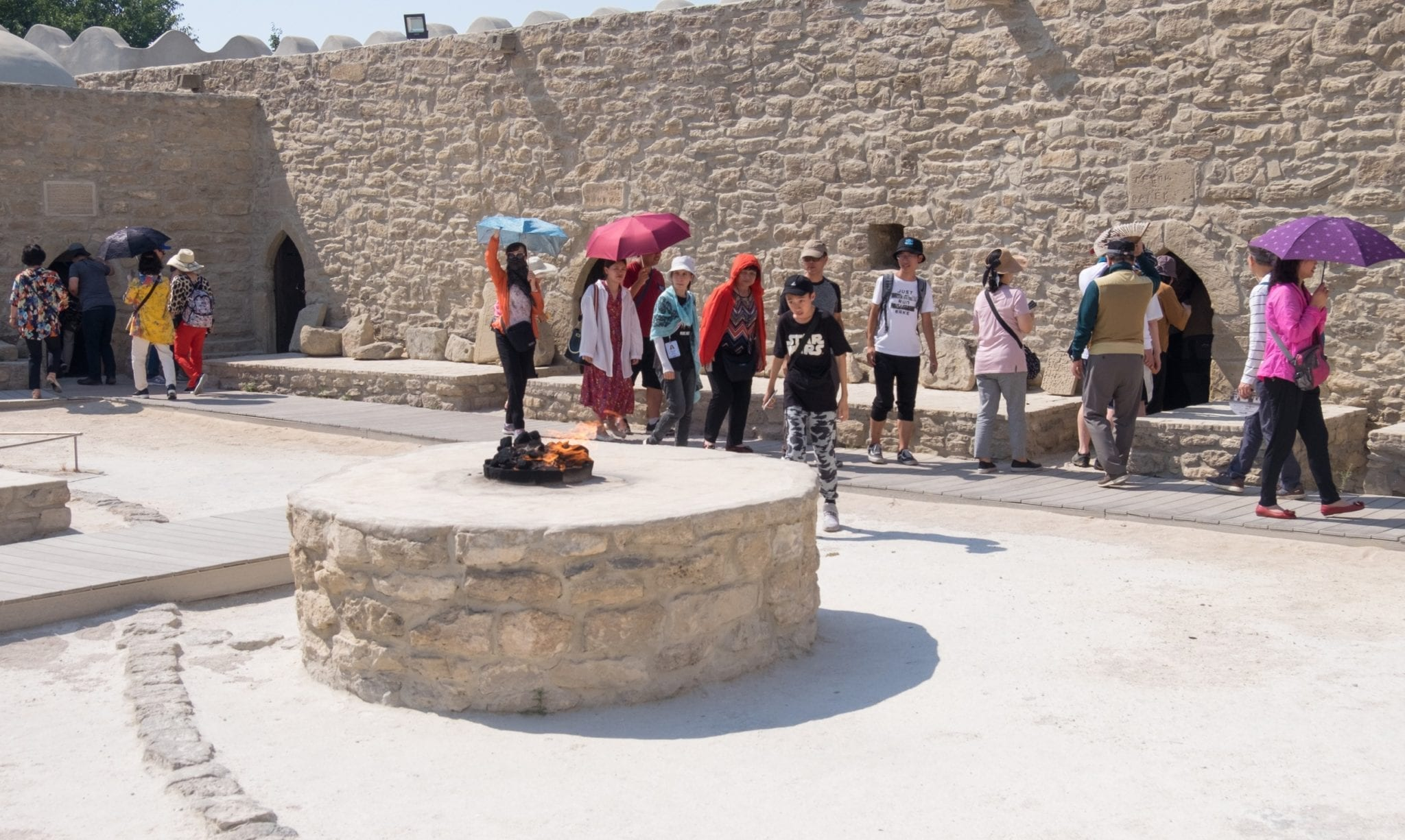 Fire bursts out of a well-like opening at Ateshgah Temple; behind it, tourists walk in a line and explore.