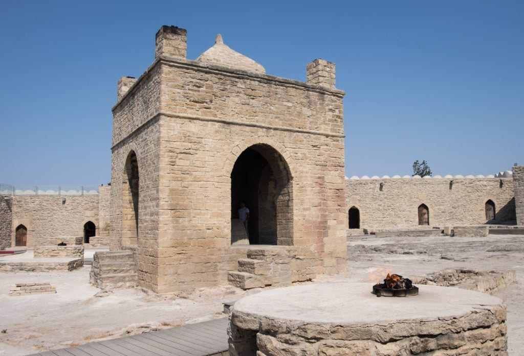 The temple at Ateshgah: a sand-colored temple set against a blue sky with a flame burning inside.