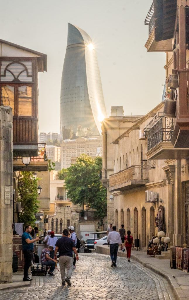 One of the metal Flame Towers of Baku curls in the background; in the foreground is the traditional sand-colored Old Town.