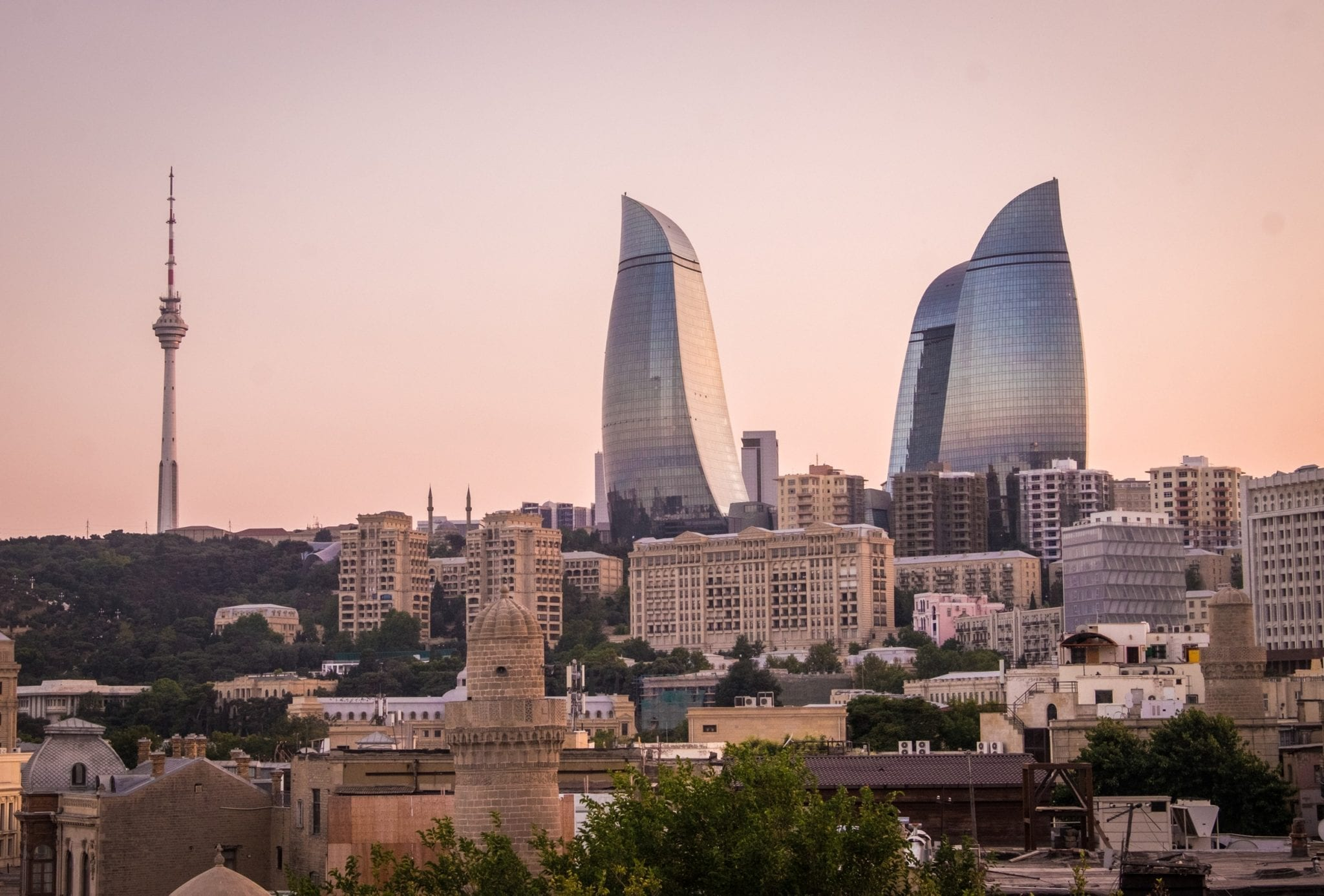 The three Flame Towers in Baku, Azerbaijan look blueish-purple against a pink sky at dusk. Underneath are smaller buildings and to the left is the city's tall, skinny TV tower.